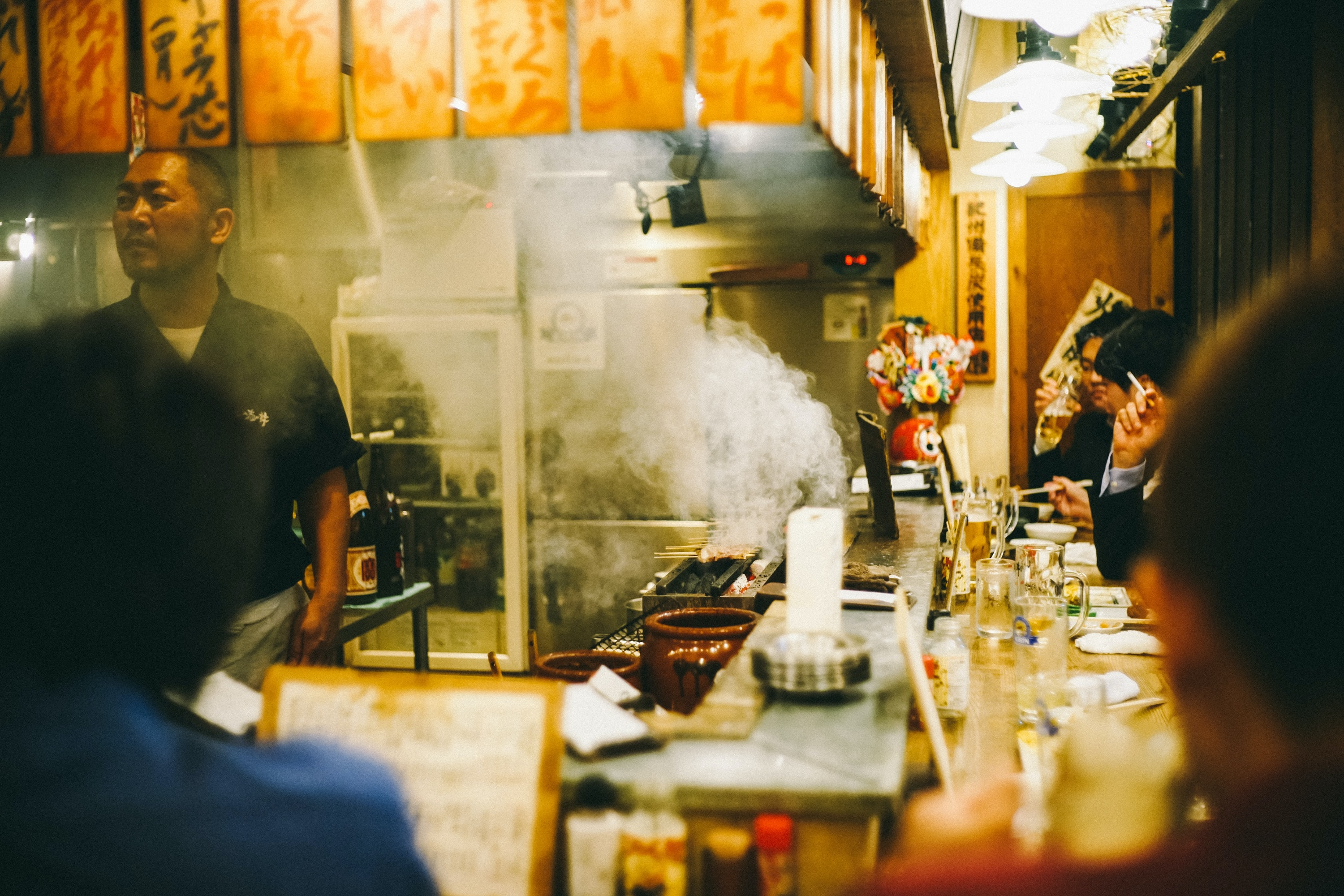 A chef cooking food for people eating at a smokey restaurant in Shinjuku