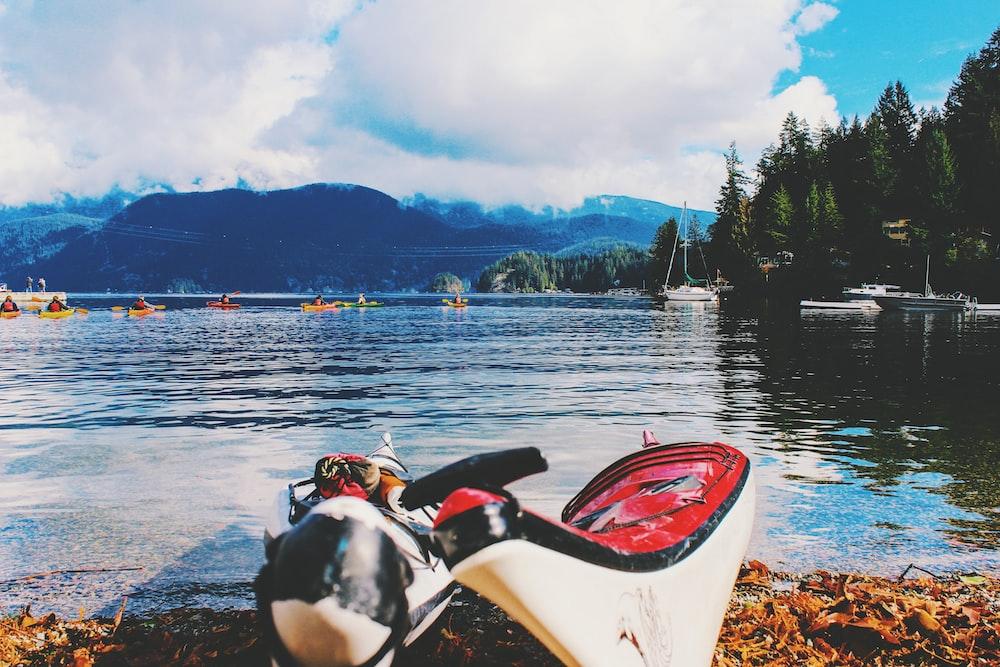 two white kayaks along body of water