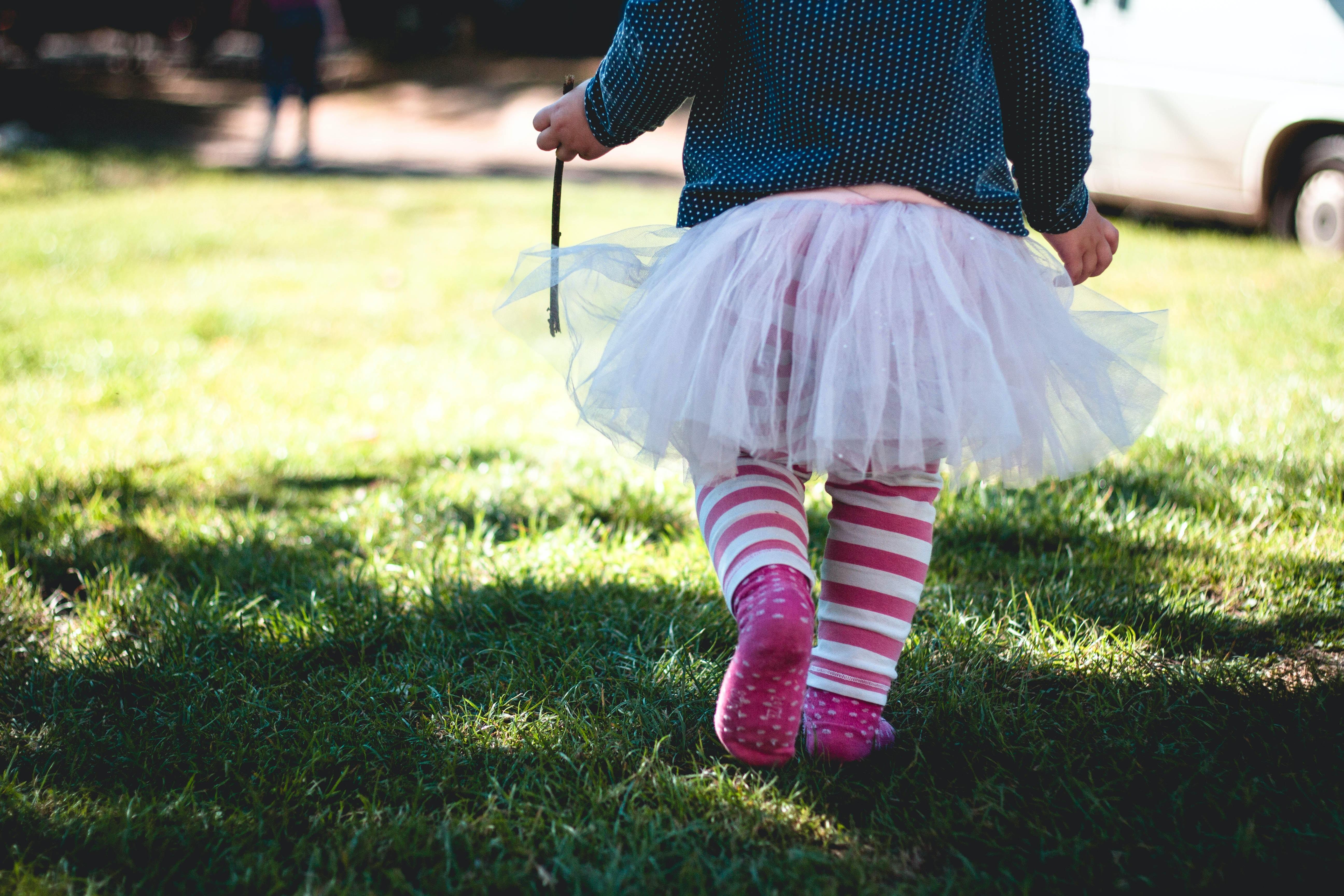 Female child wearing a tutu with stripe leggings walks on grass towards sunlight holding a stick
