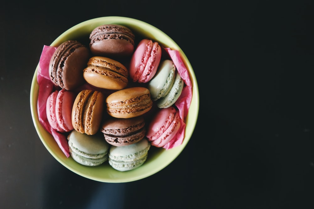 Colored cookies with frosting in the middle, sitting in a bowl.