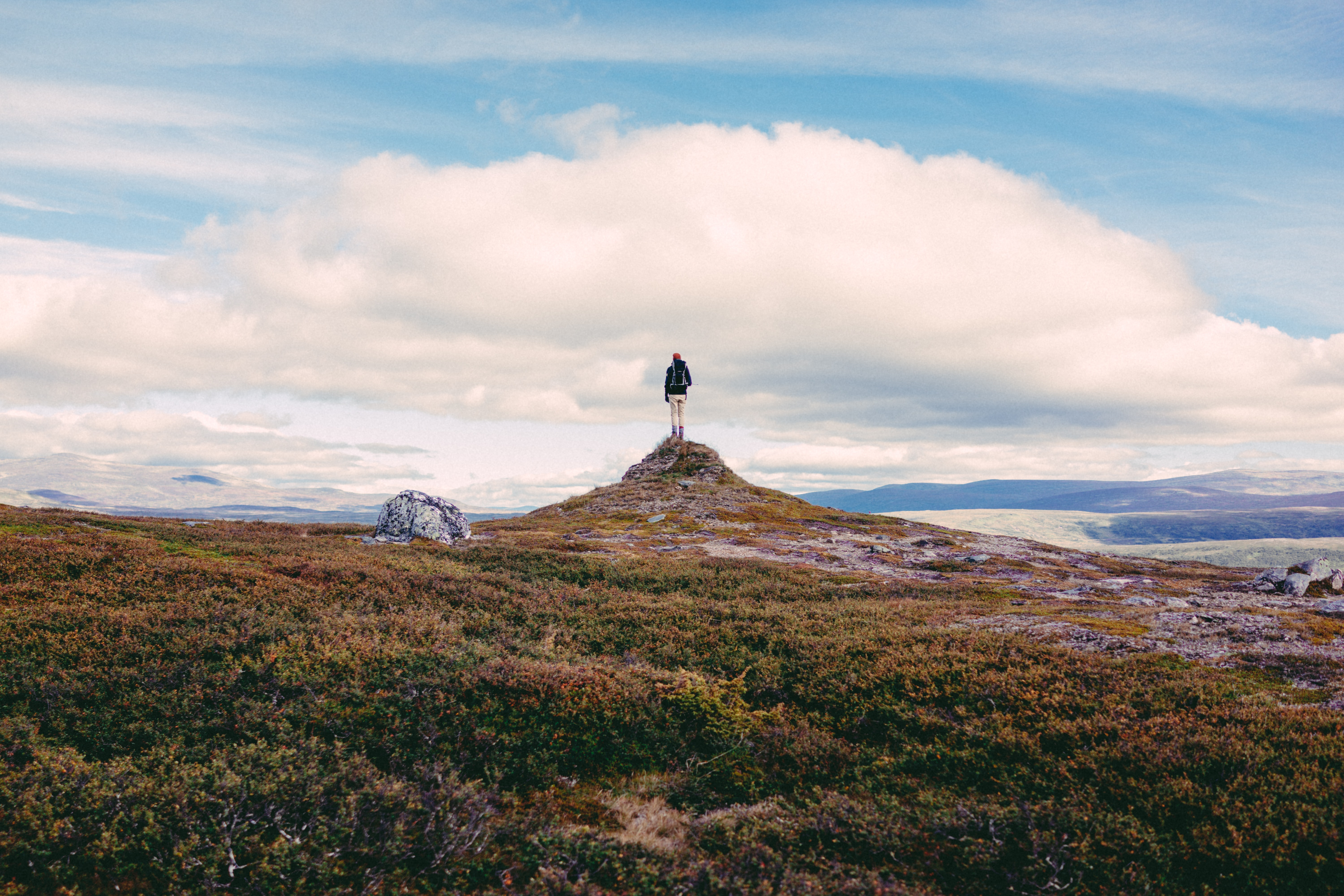A lone hiker on top of a small rock tower  in a shrub-covered plain in Helagsfjället