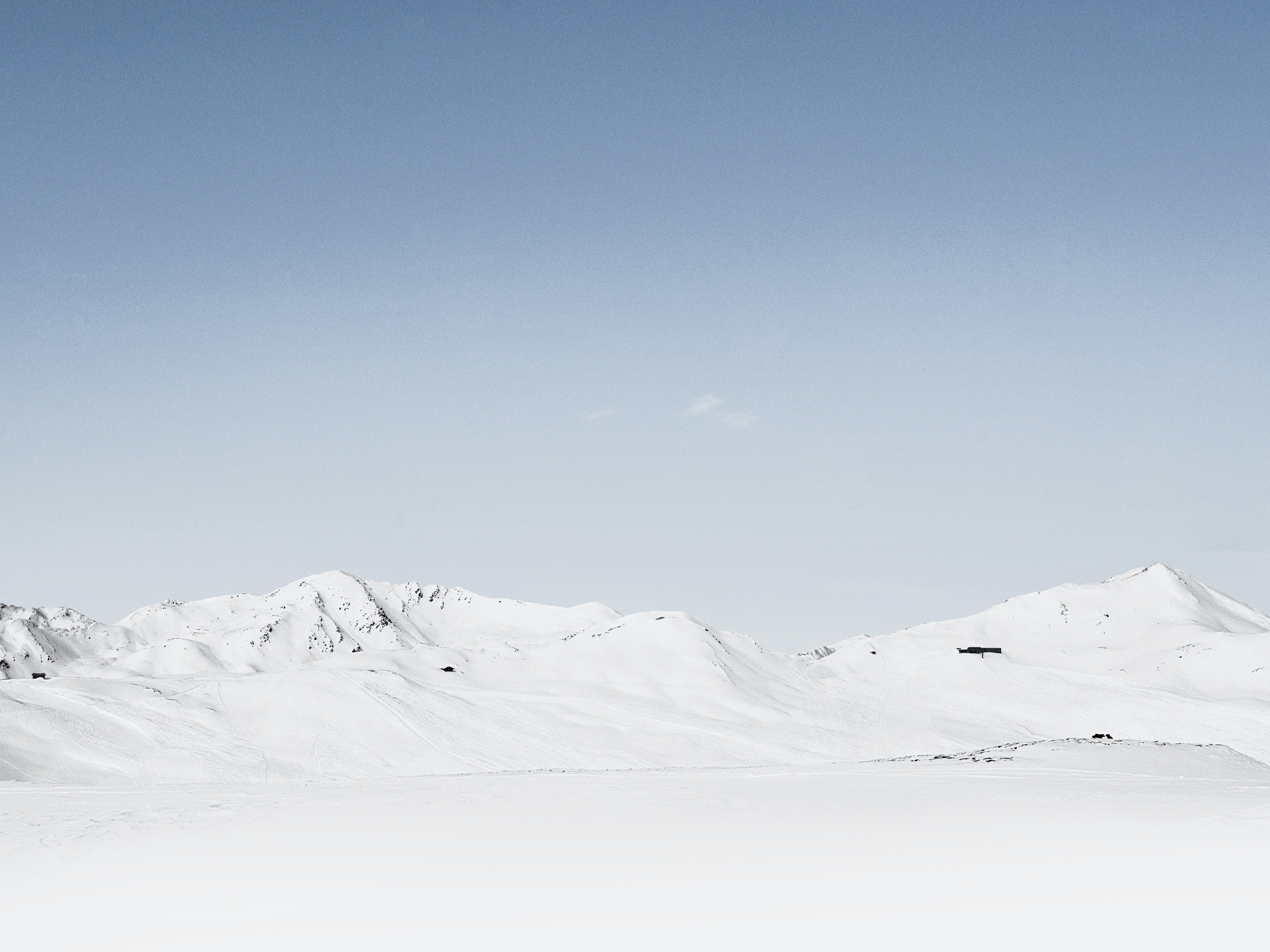 A mountain ridge under a snow blanket on a cloudless day