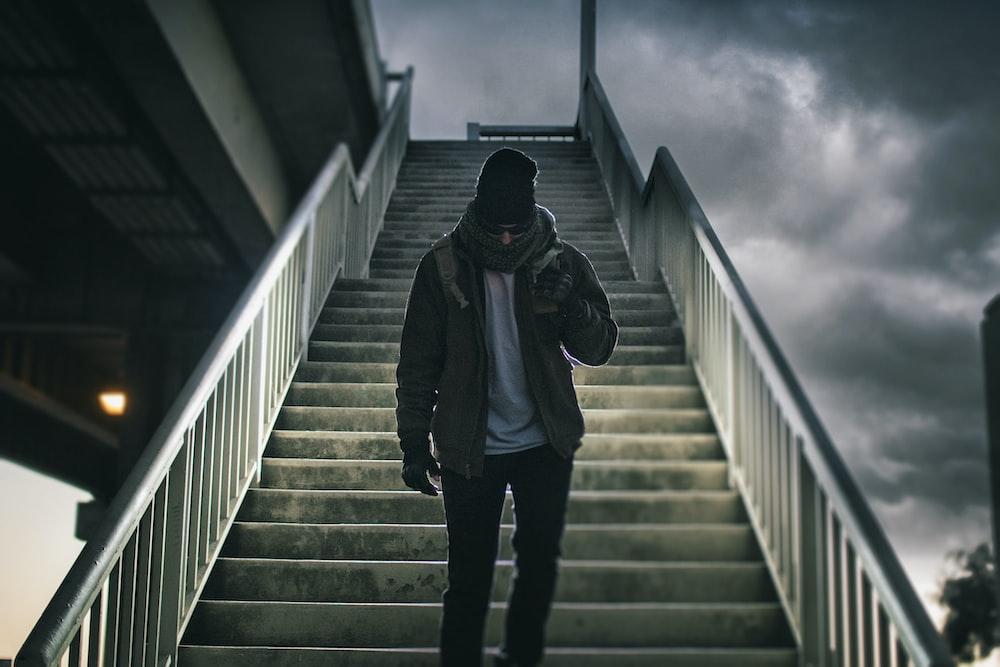 man wearing brown jacket walking on the stair under black sky