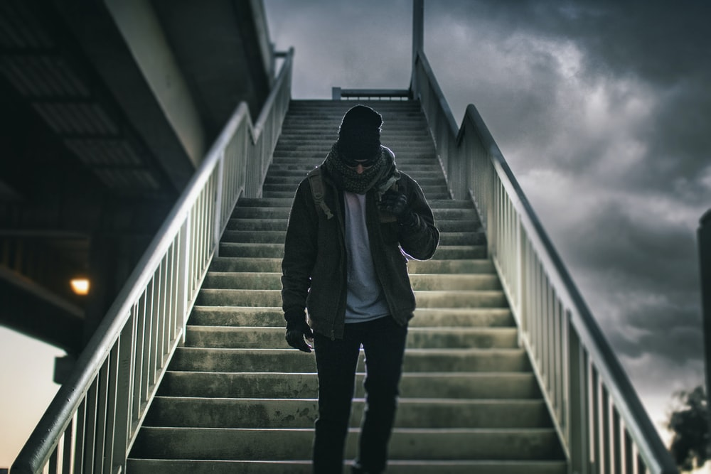 man wearing brown jacket walking on the stair under black sky
