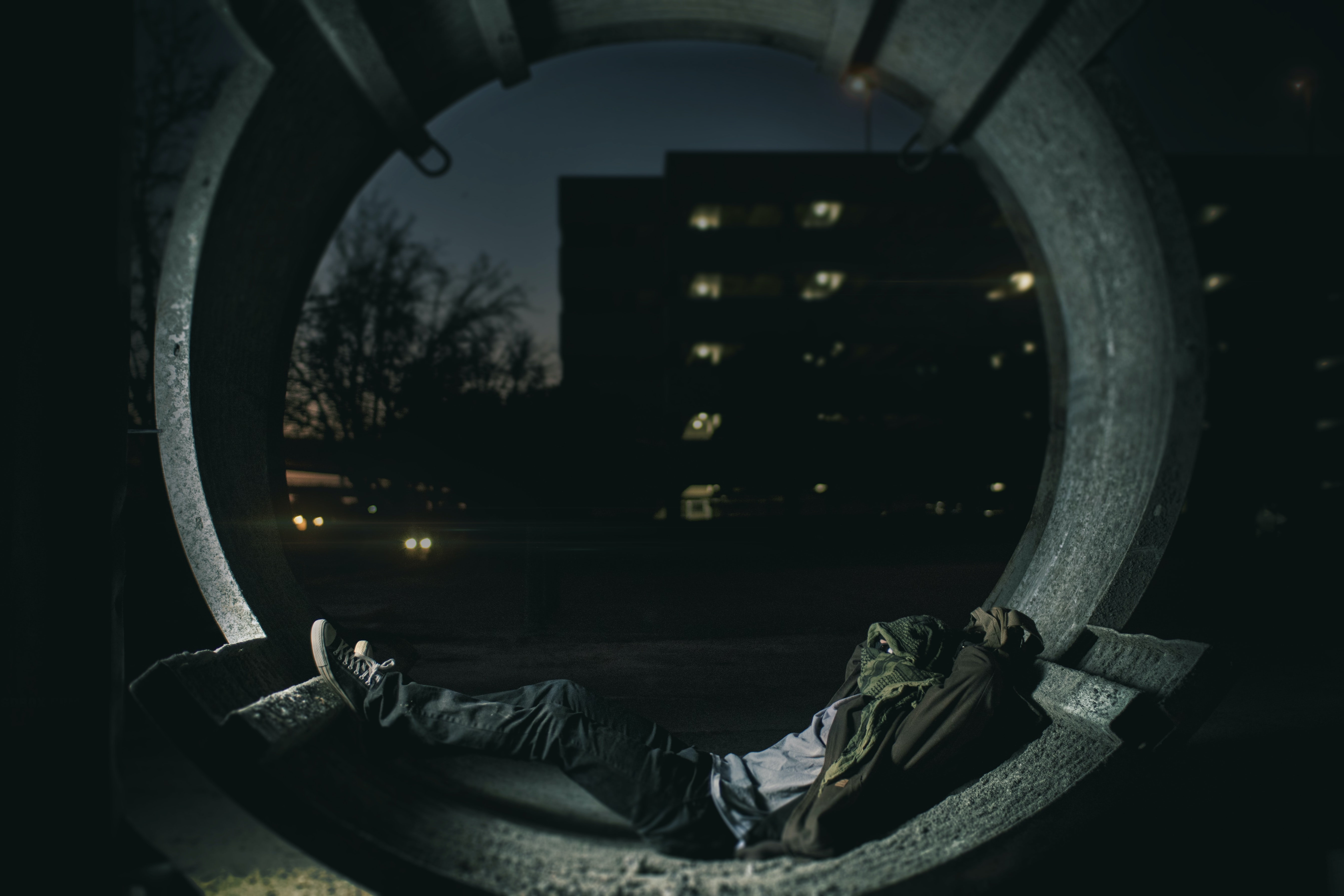 Homeless person in an urban area sleeps in a circular structure near a building with lights