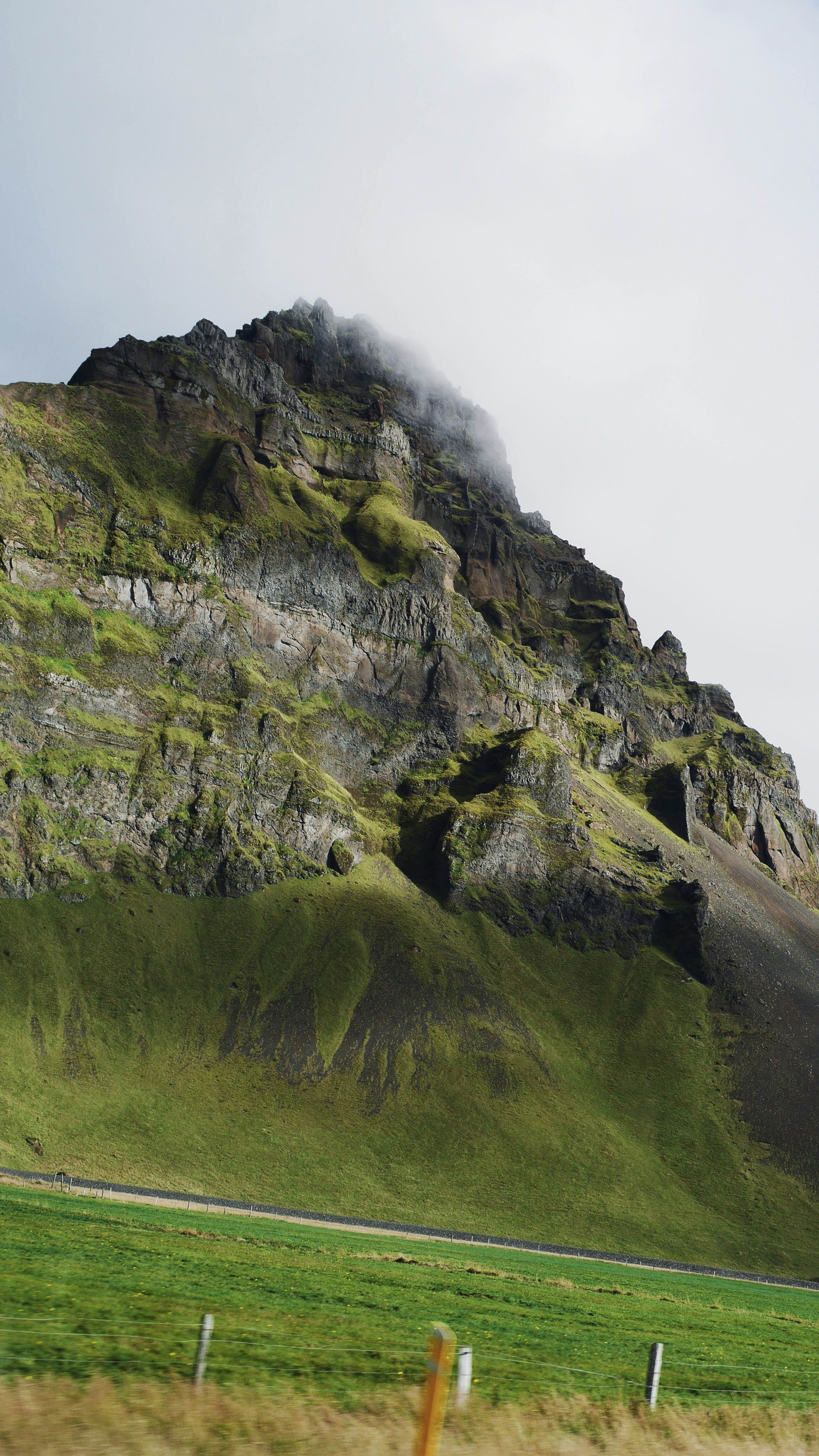 A craggy mountain with its top shrouded in fog rising above an asphalt road