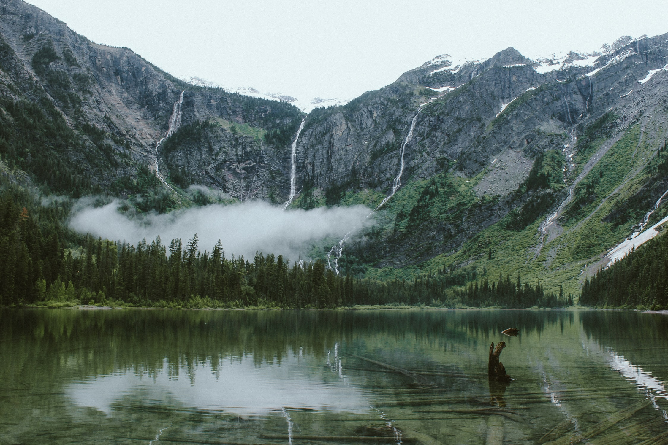 The clear surface of Avalanche Lake in a mountain basin