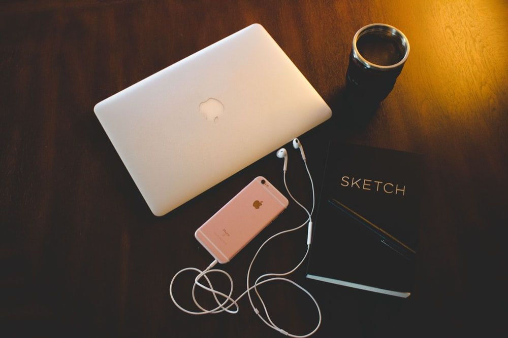 silver MacBook and rose gold iPhone 6s