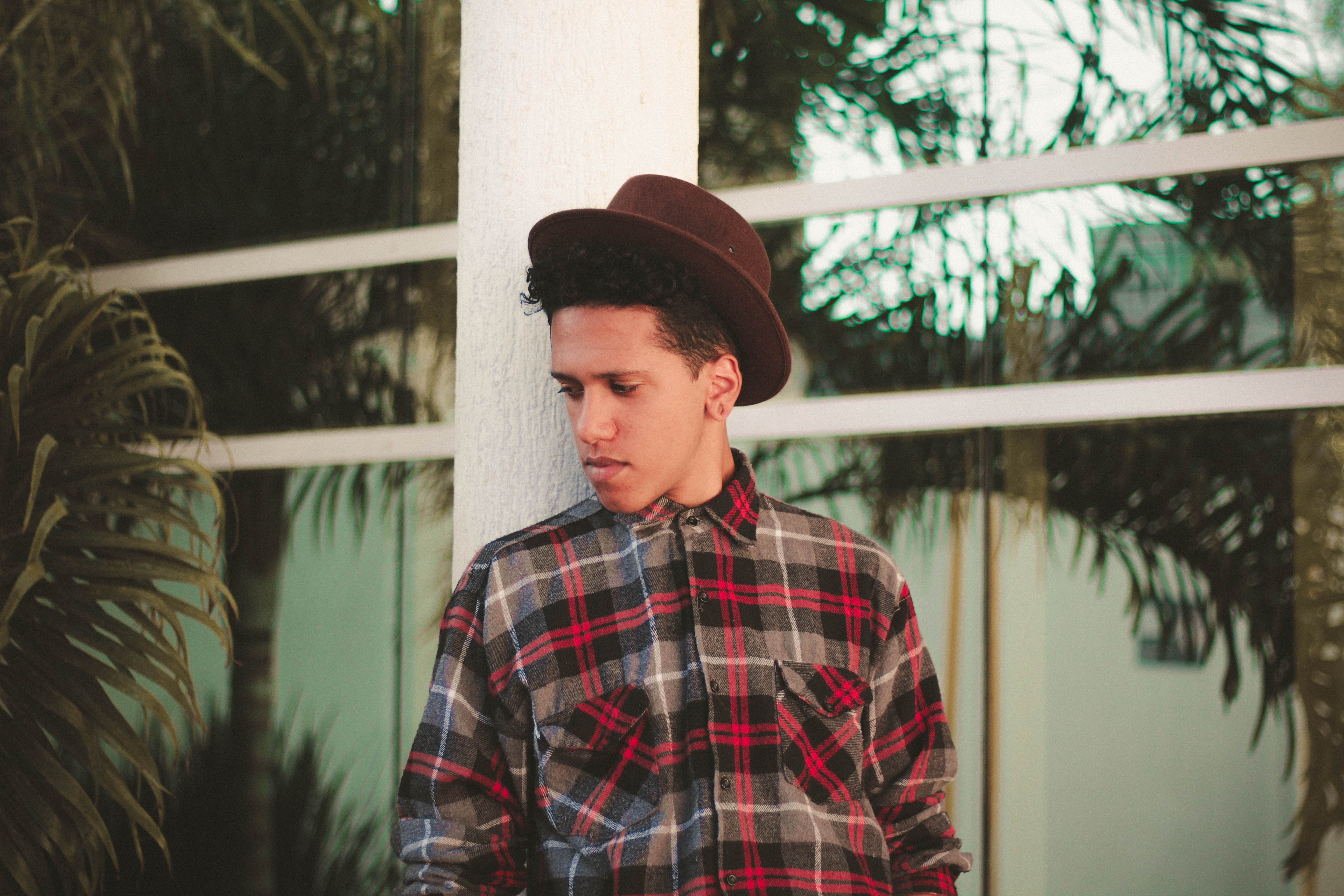 Trendy man with a hat and plaid shirt leaning against a railing