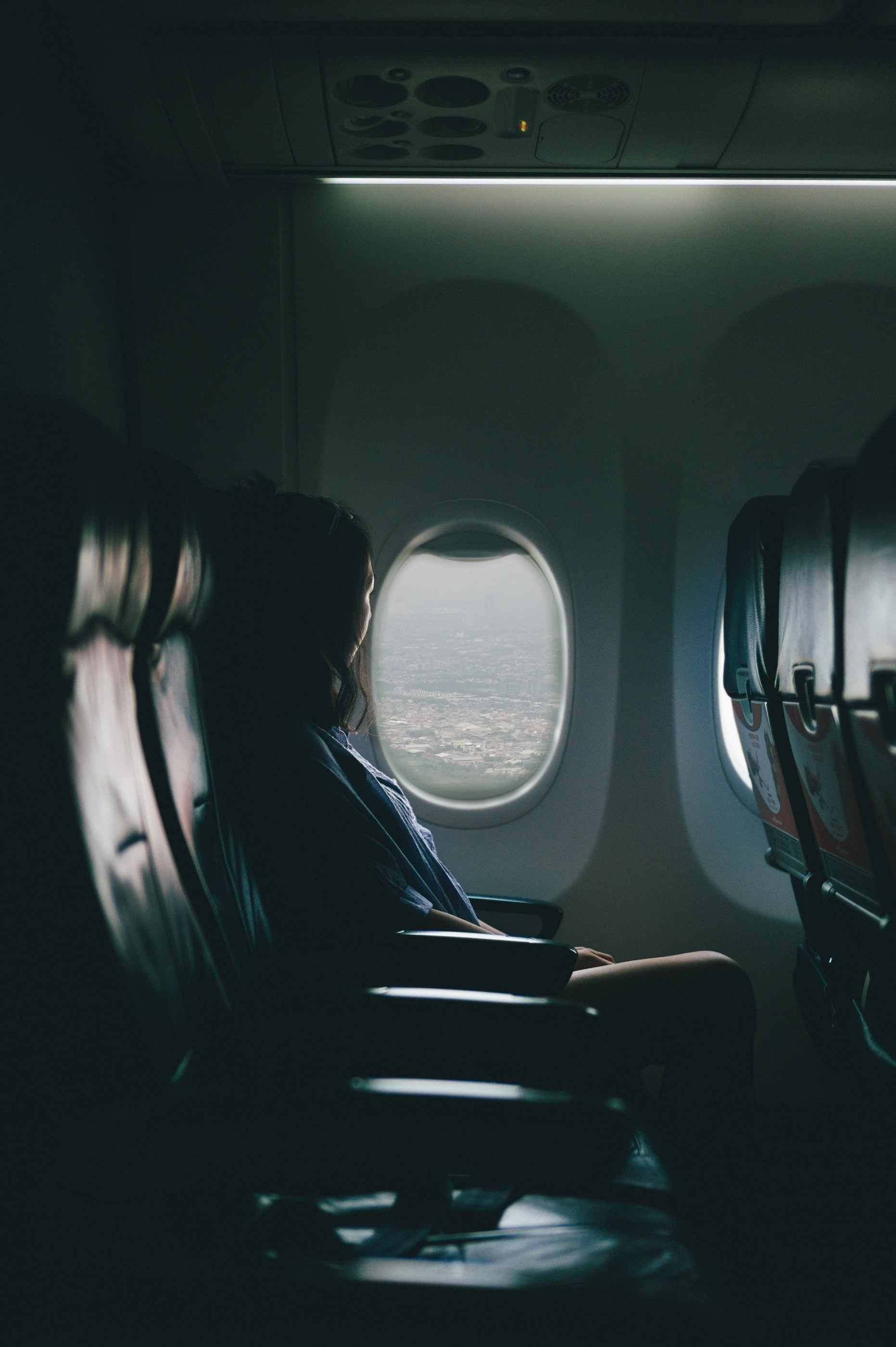 A woman looking out of an airplane window while flying over a city