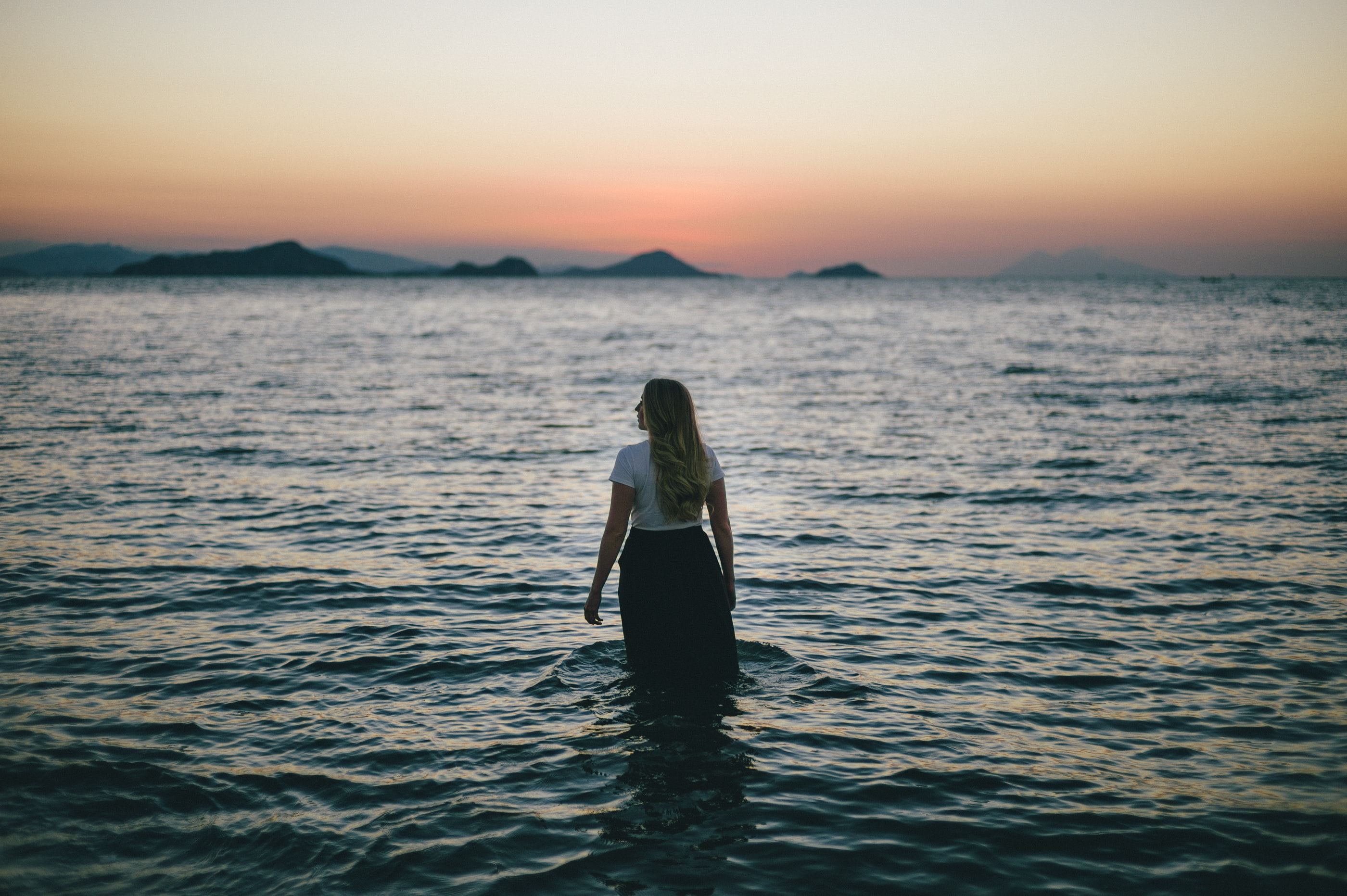 The back of a woman standing knee-deep in the ocean looking into the distance at dusk