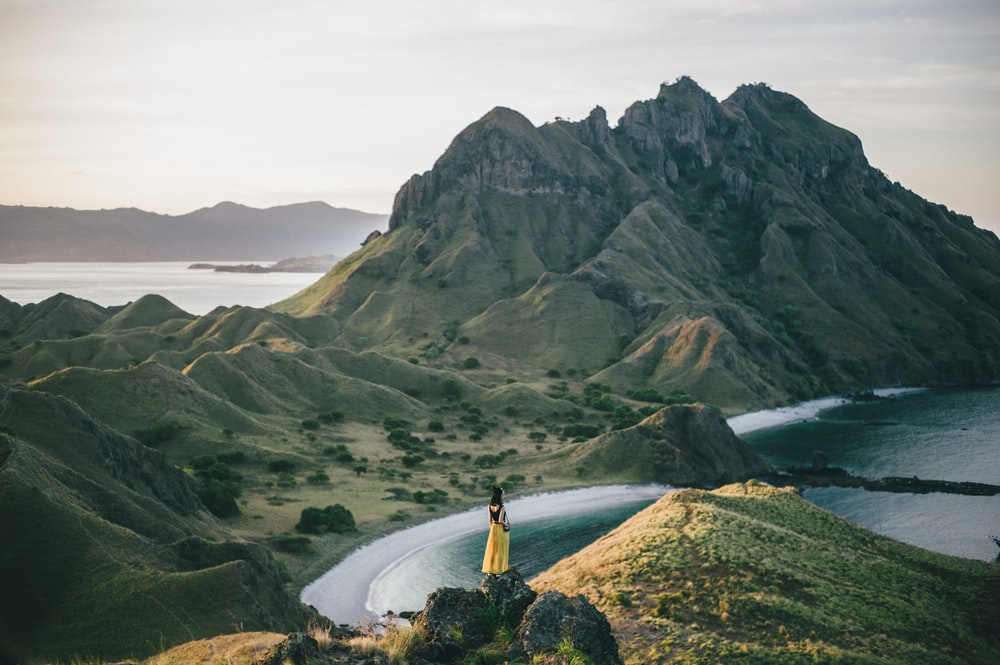 woman standing on mountain near body of water