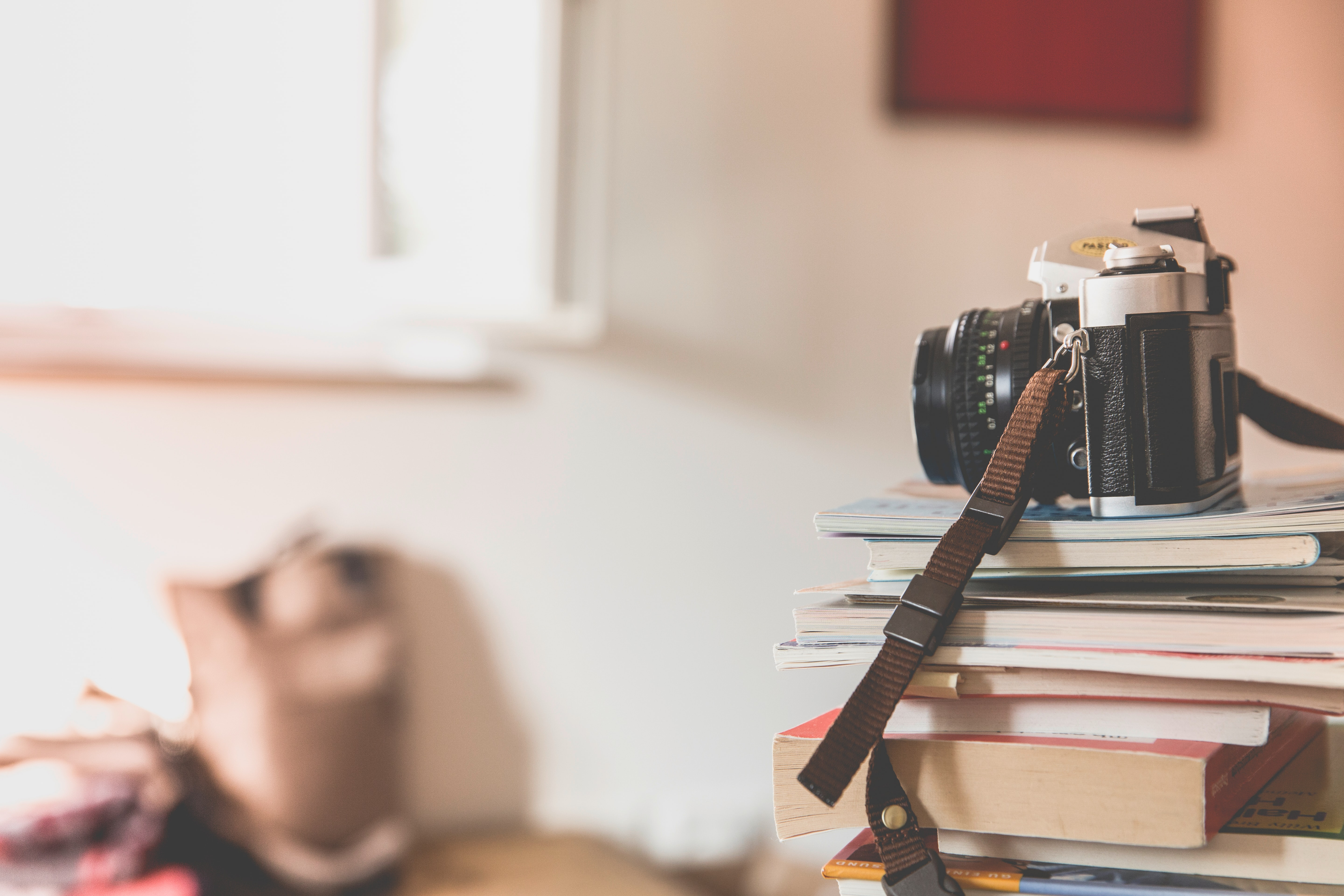 A camera with strap and lens sits on top of a stack of books and magazines