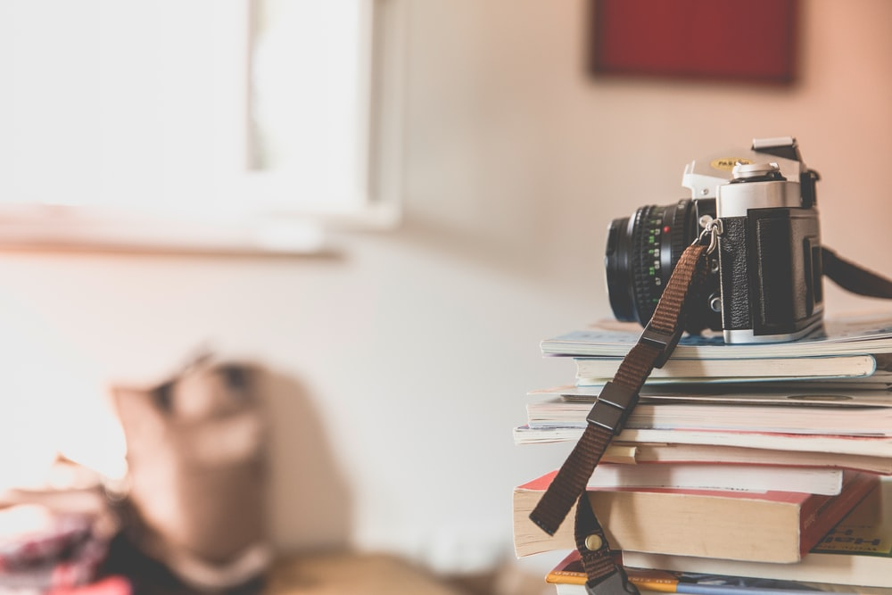 black film camera on top of piled books inside well lighted room