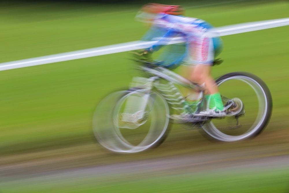 person biking on green field