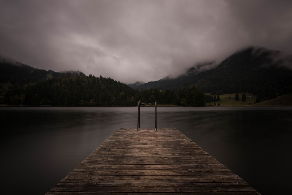 brown wooden dock near lake under cloudy sky
