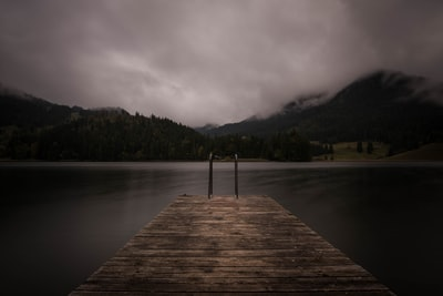 brown wooden dock near lake under cloudy sky moody teams background