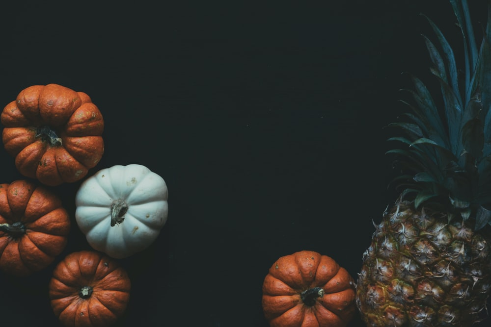 four orange and white pumpkin squashes and one pineapple