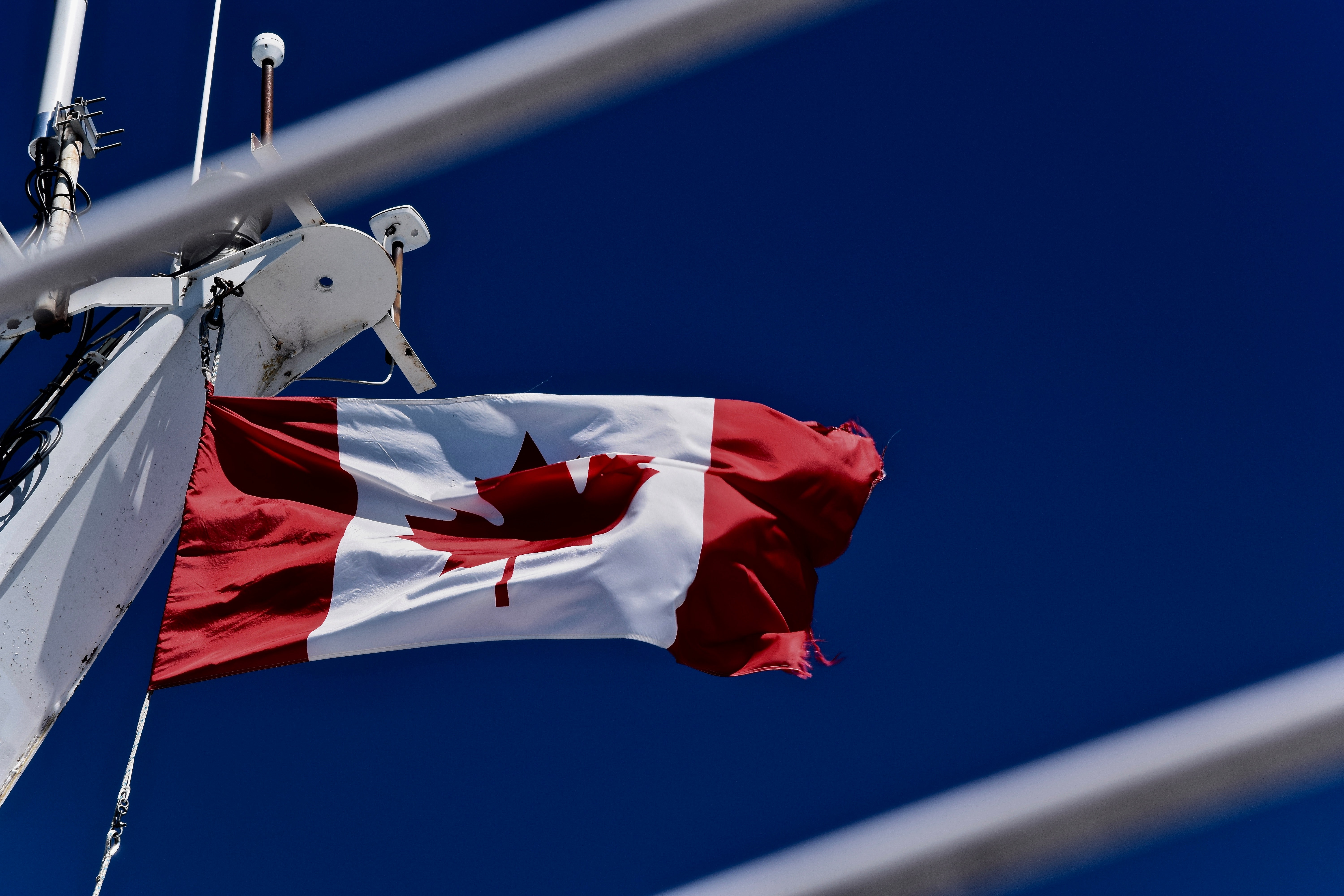 Canadian flag flying on a flagpole by industrial beams