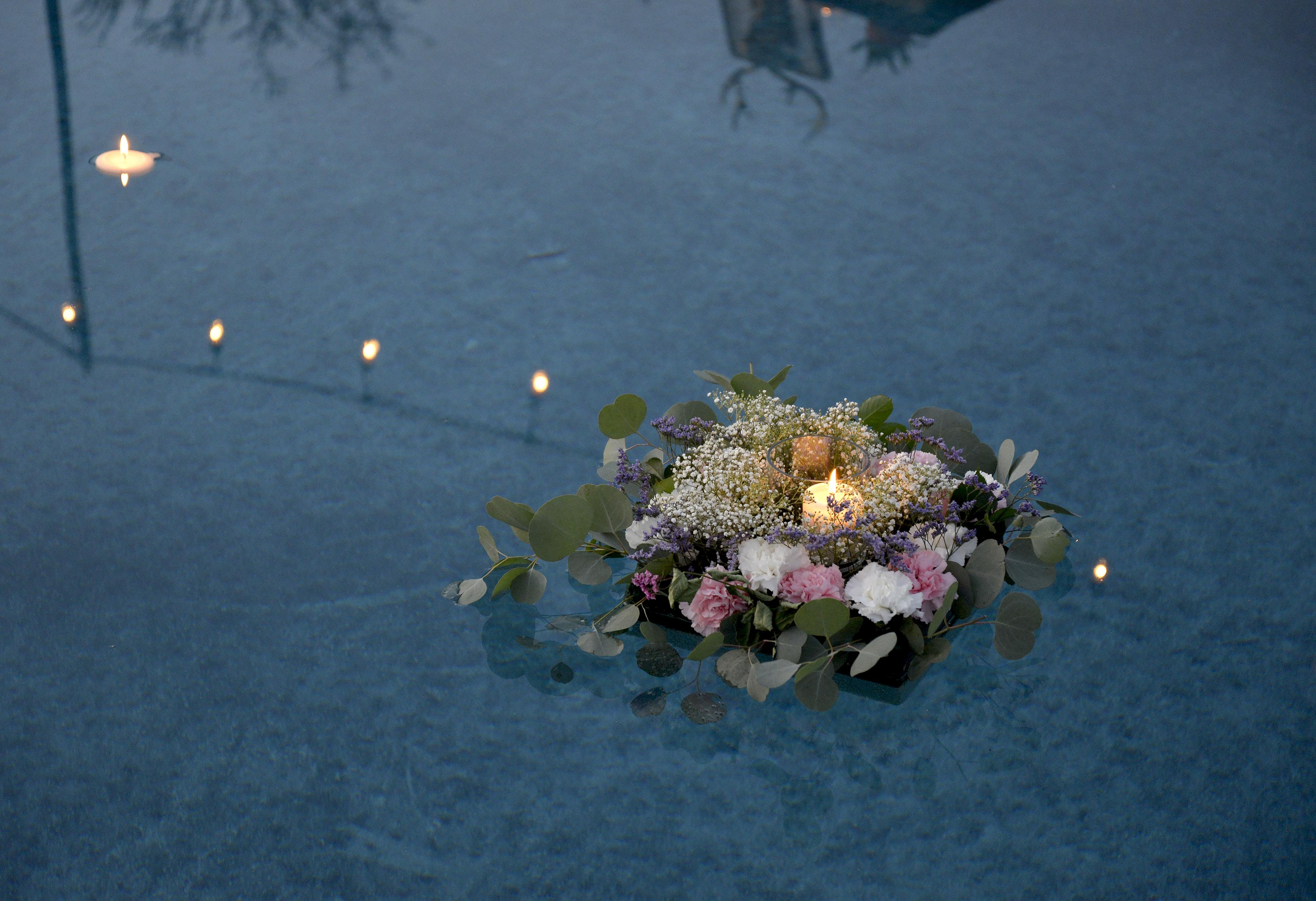 A box with a burning candle surrounded with various flowers and leaves floating on the surface of water