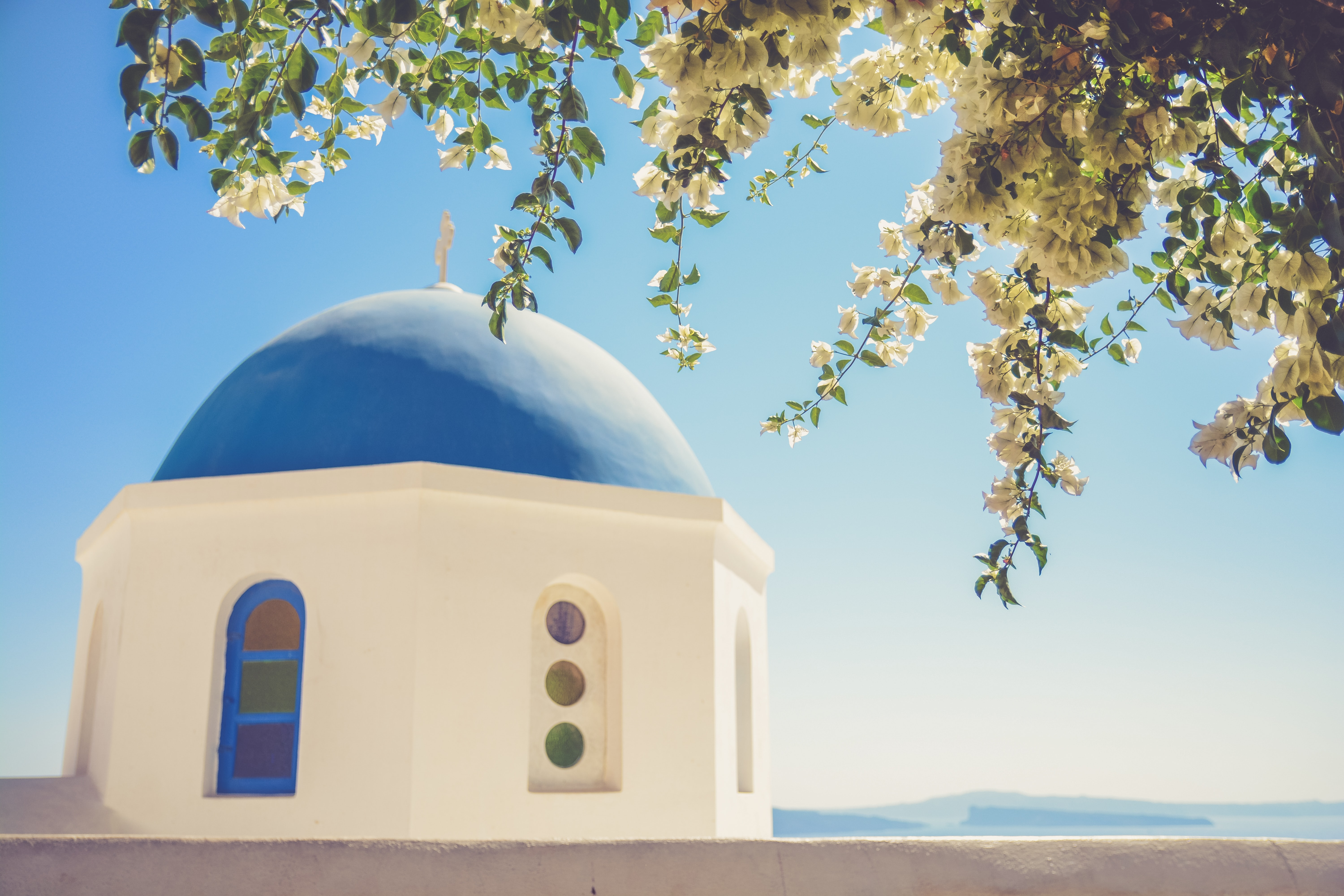 A blue dome on a Mediterranean building near a flowering tree