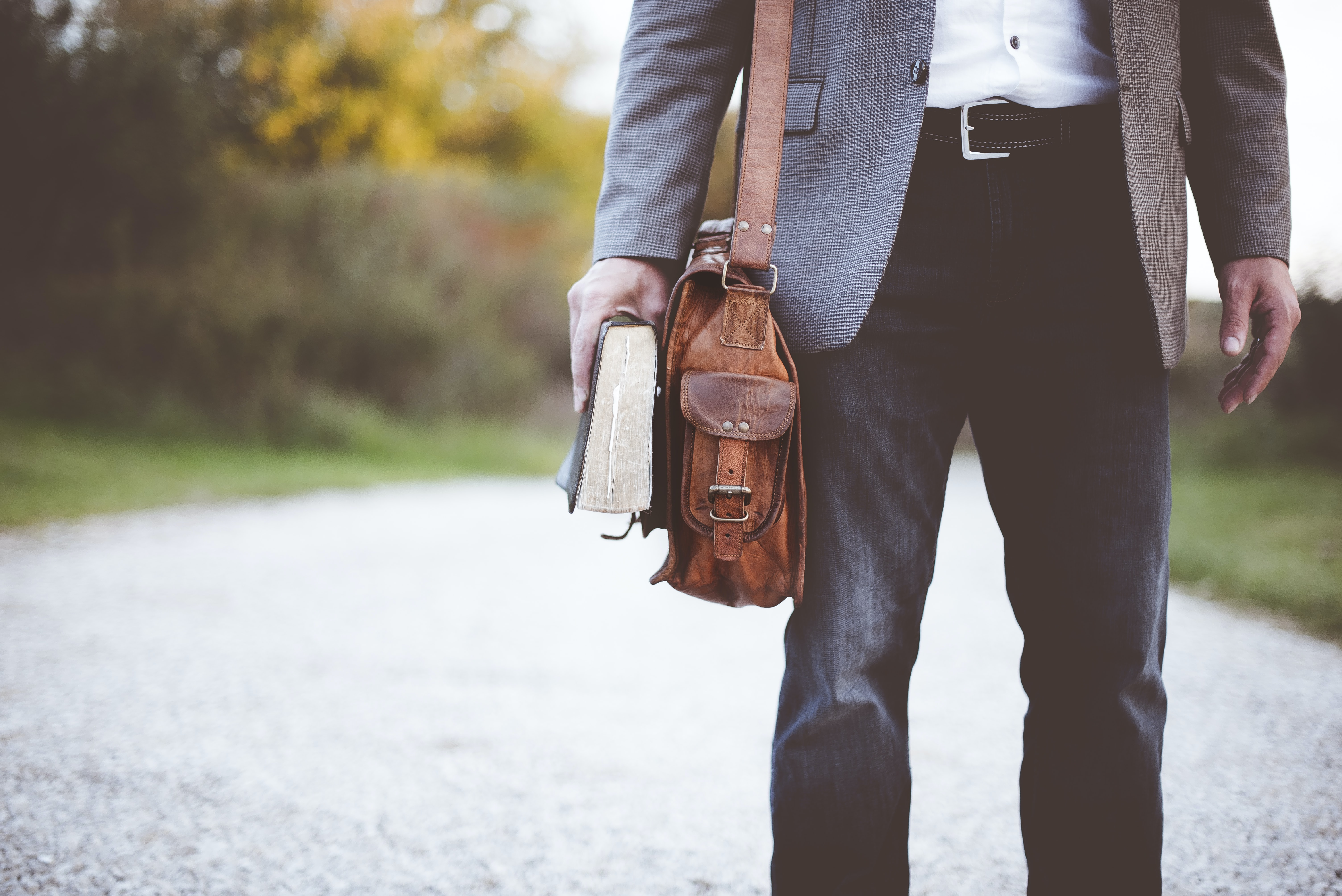 A low shot of an elegantly dressed man with a leather bag holding a book in his hand