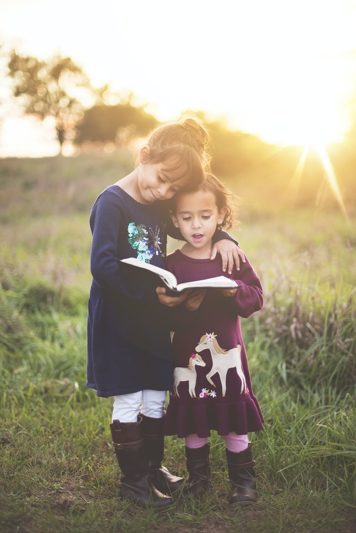 Young children reading book together