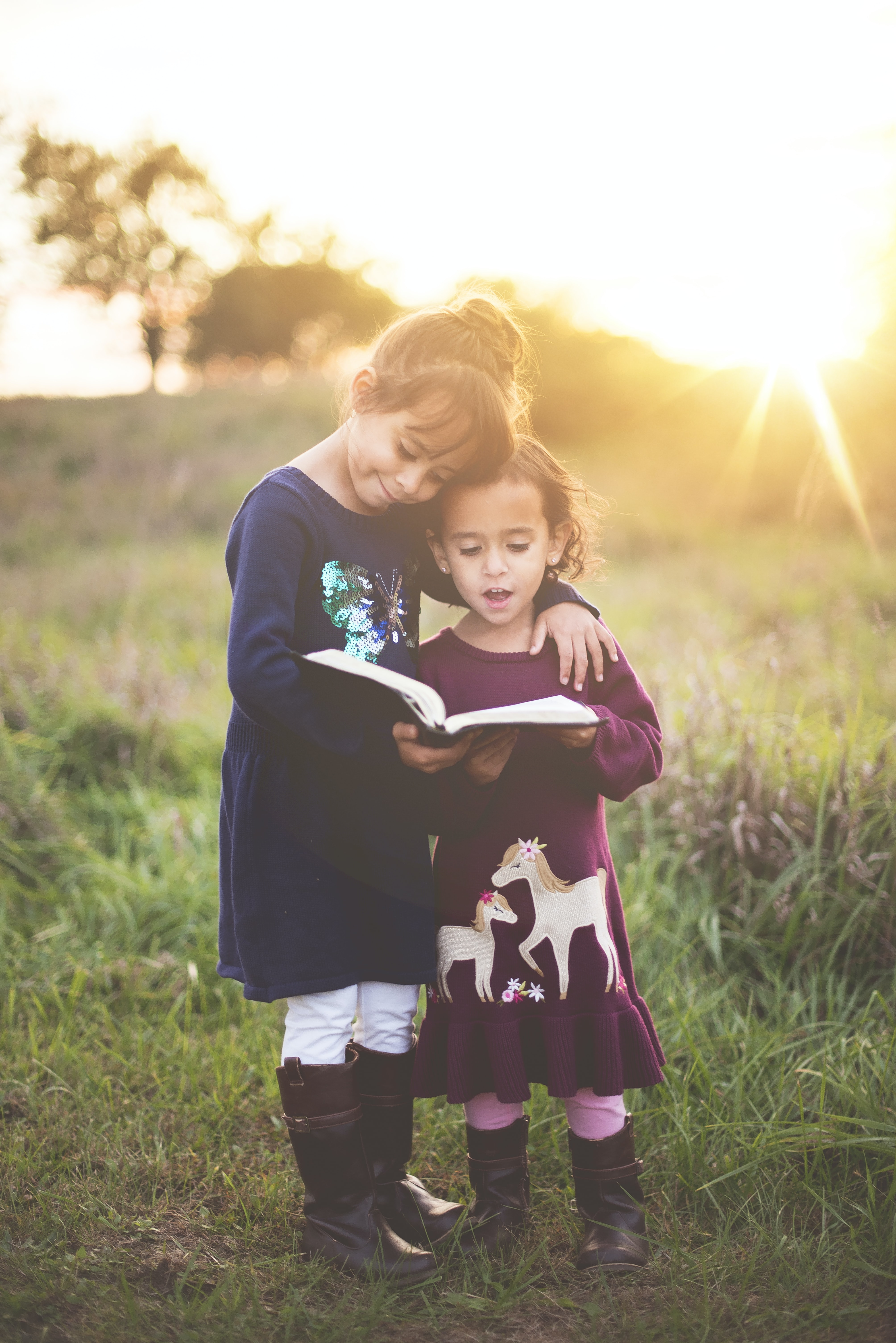 Two young girls stand reading from a book outdoors in the sun