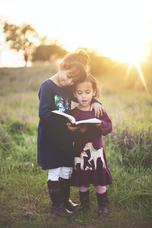 A photo of two children, a girl and a boy who is younger. The boy is holding a book and the girl has her arm around his shoulders and is looking at the book as well. They are in a beautiful field.