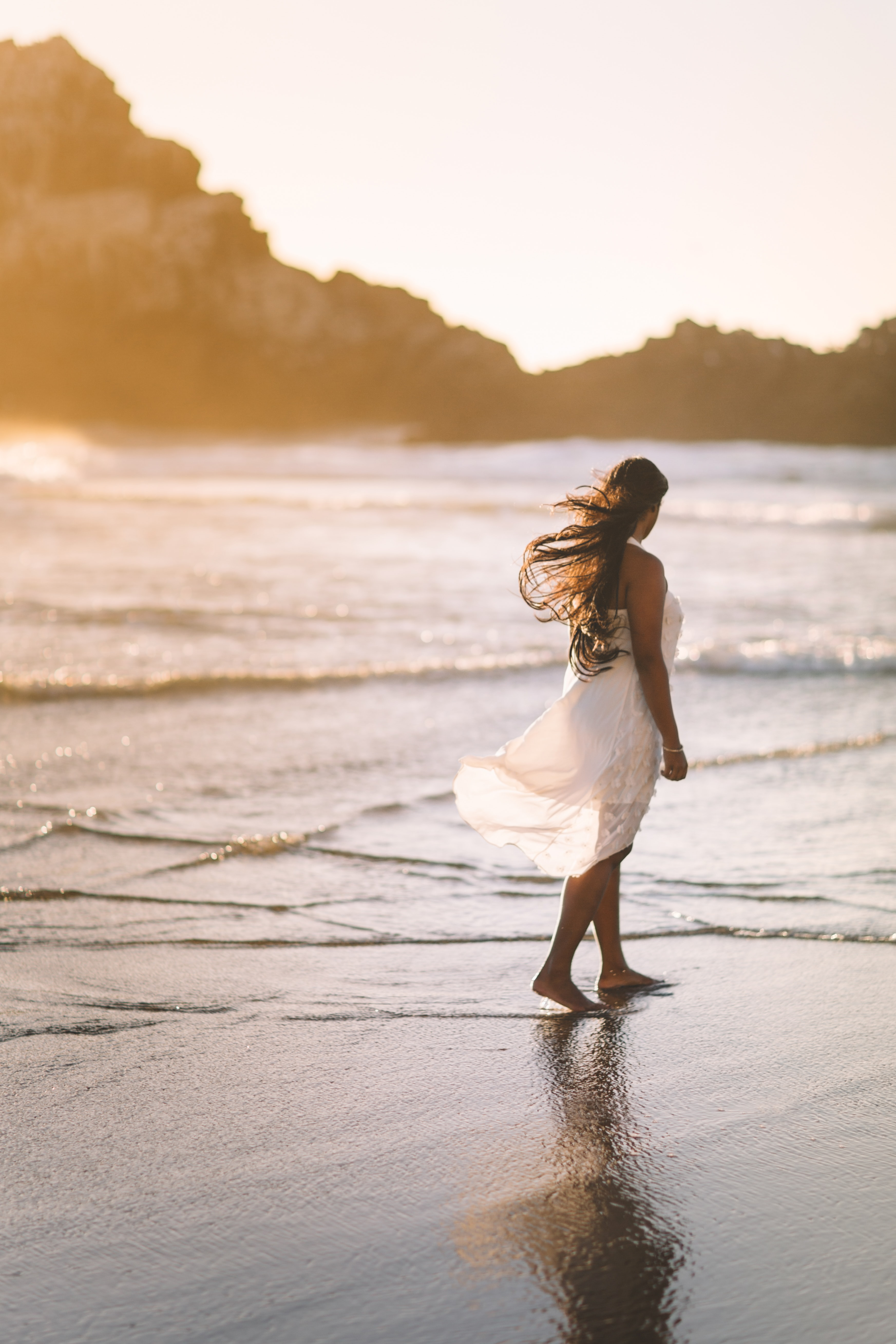 selective focus photo of woman standing on sea shore near rock formation during golden hour
