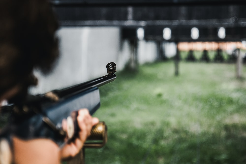 person aiming on the gun