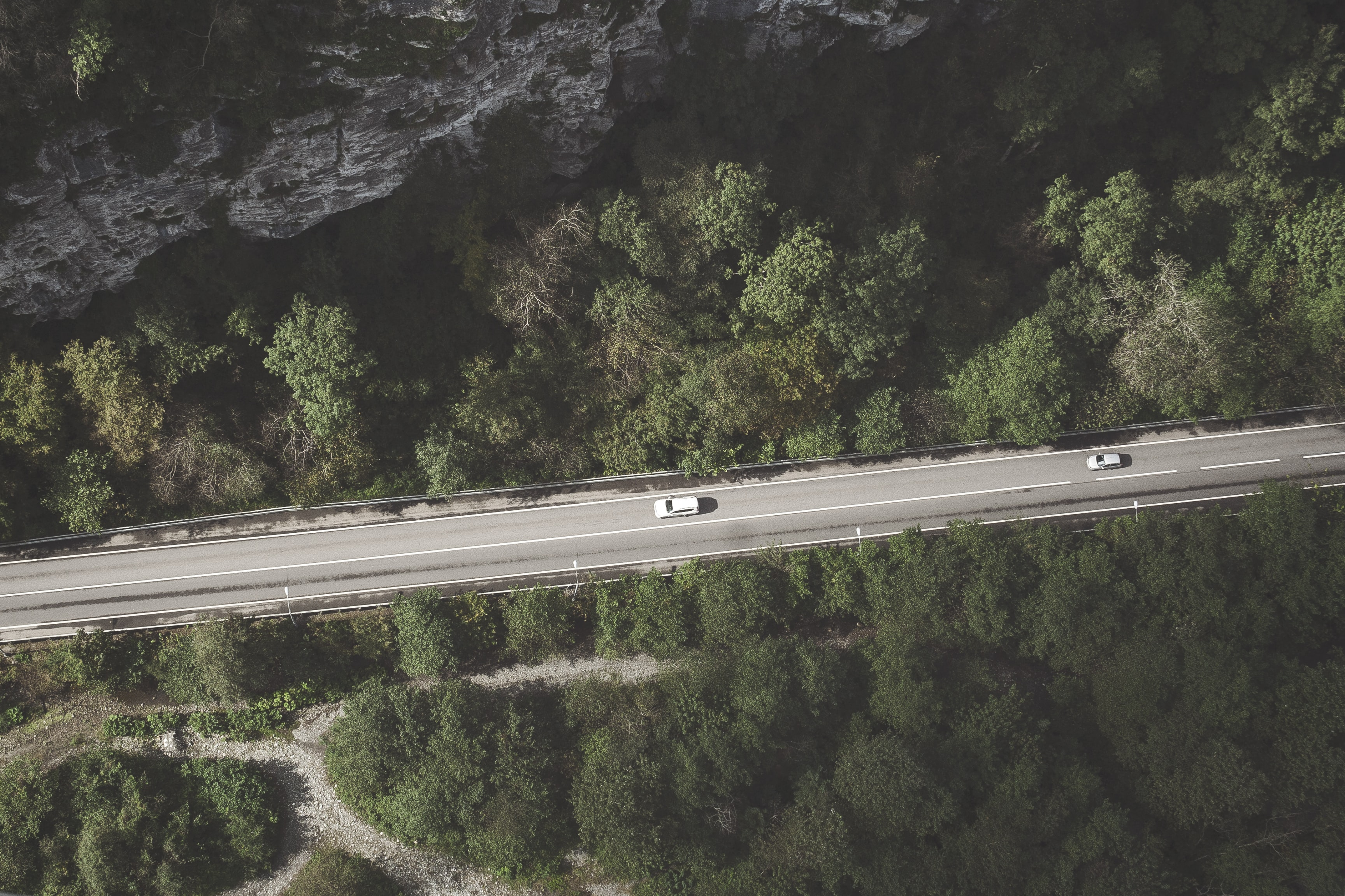 Drone shot of two cars on the highway surrounded by hills.
