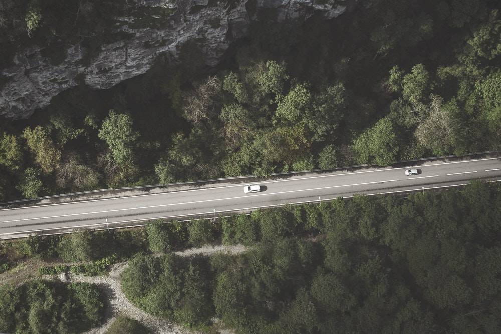 aerial photo of gray concrete in the middle of forest with two cars