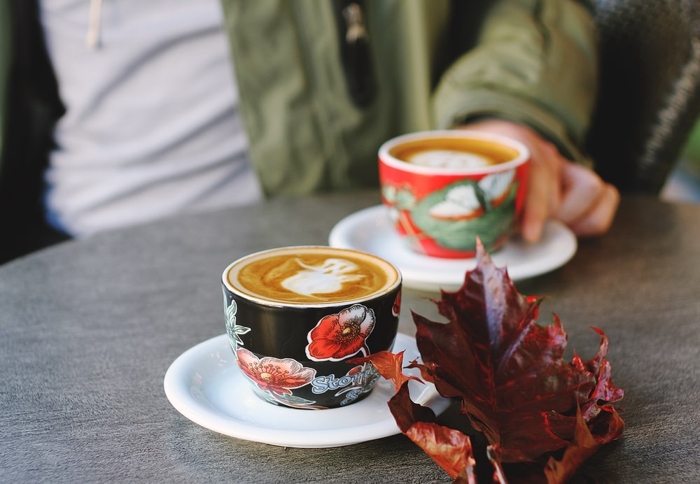 selective focus photo of black floral cup on white saucer with latte