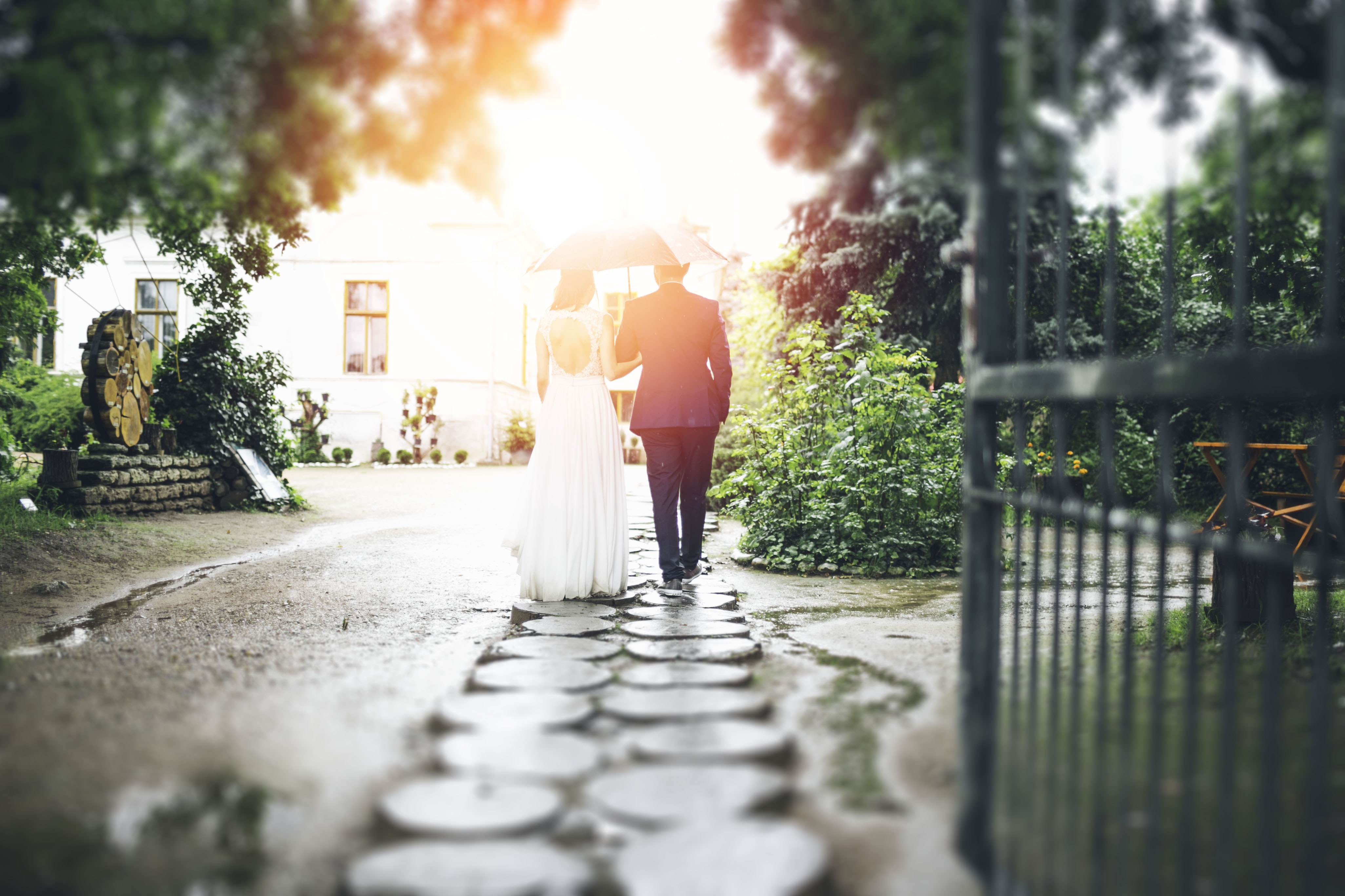 Bride and groom walking down a stone path holding an umbrella with light shining on them