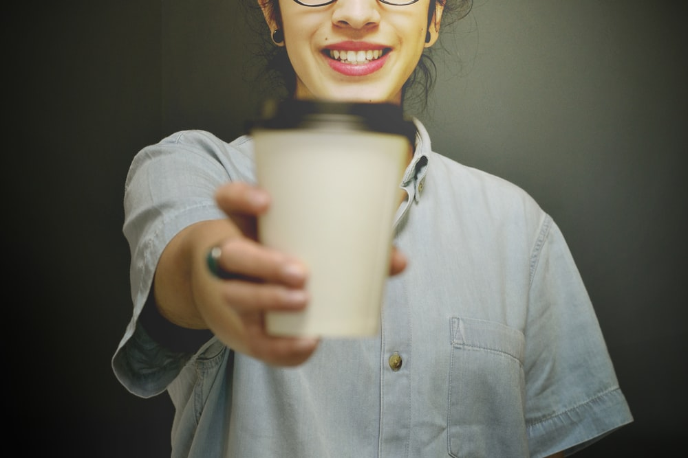 woman holding white and black coffee cup