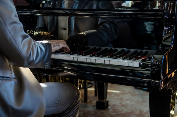 A low shot of a man in a glossy silver suit playing the piano