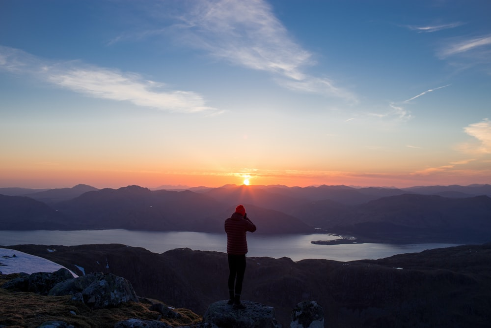 person standing on mountain ridge over lake under cloudy sky at sunset