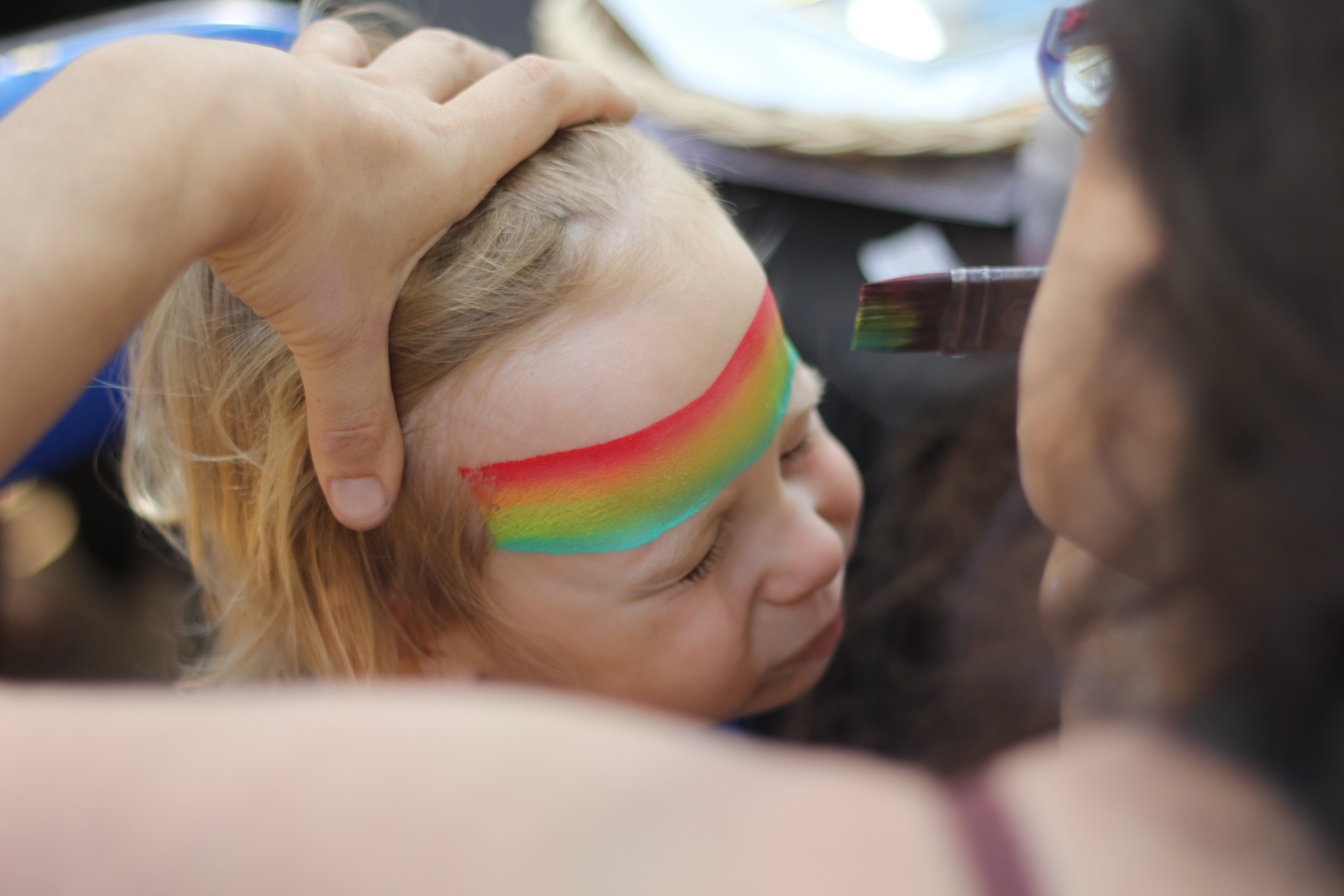 A woman painting a tri-color stripe on a child's forehead