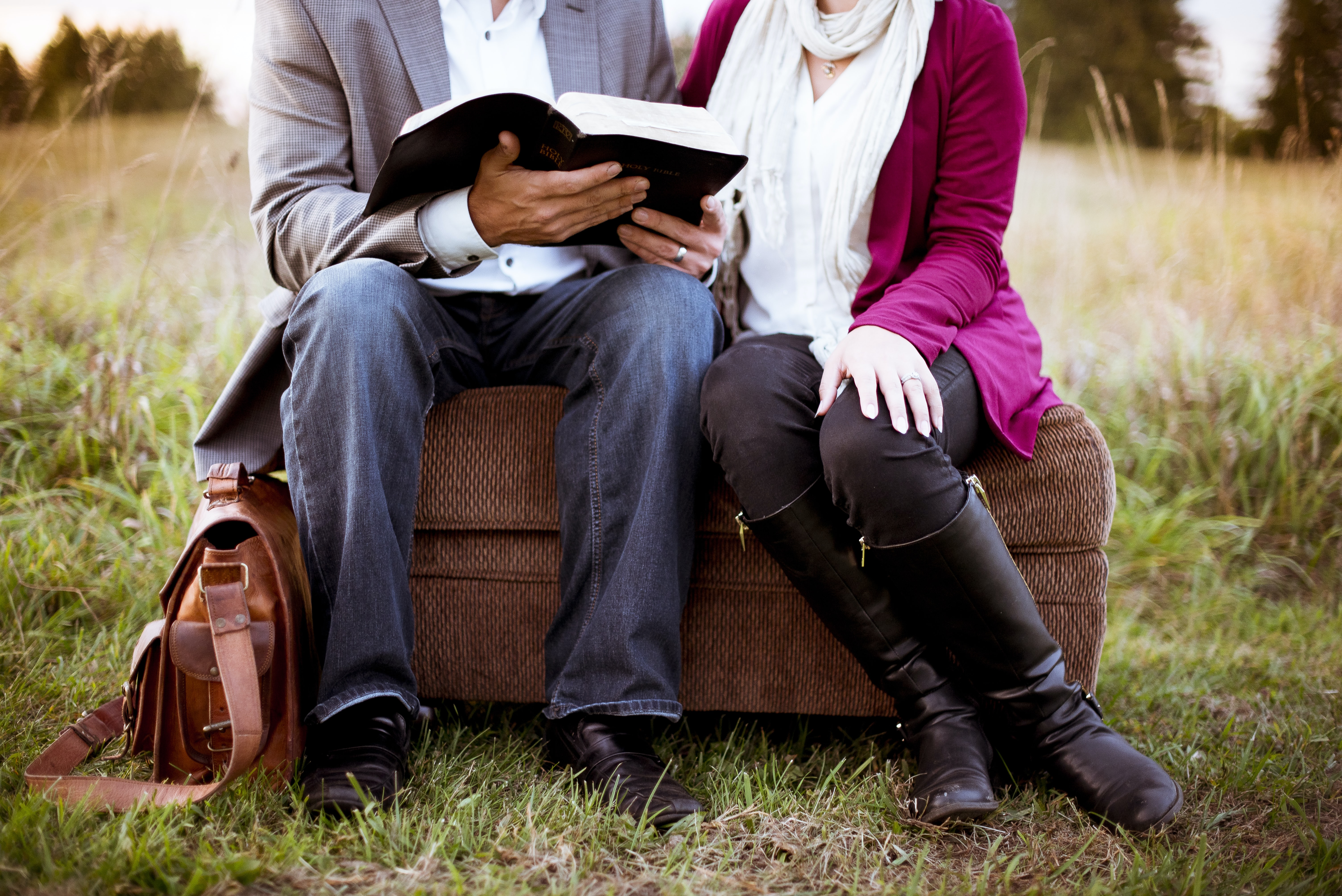 A married couple sitting on an ottoman outdoors. He is reading a book.