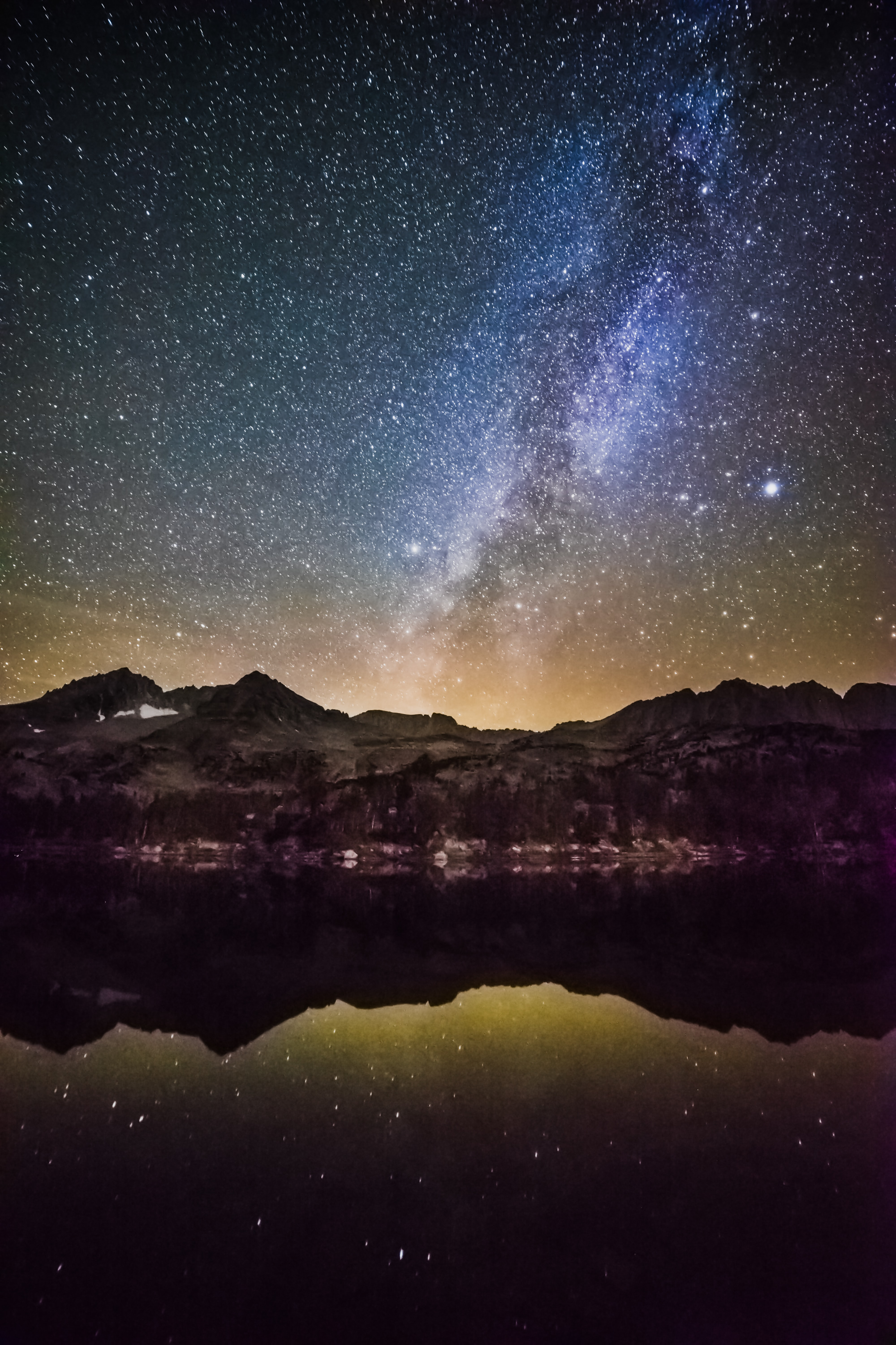 A starry sky with blue clouds above mountains and a lake.