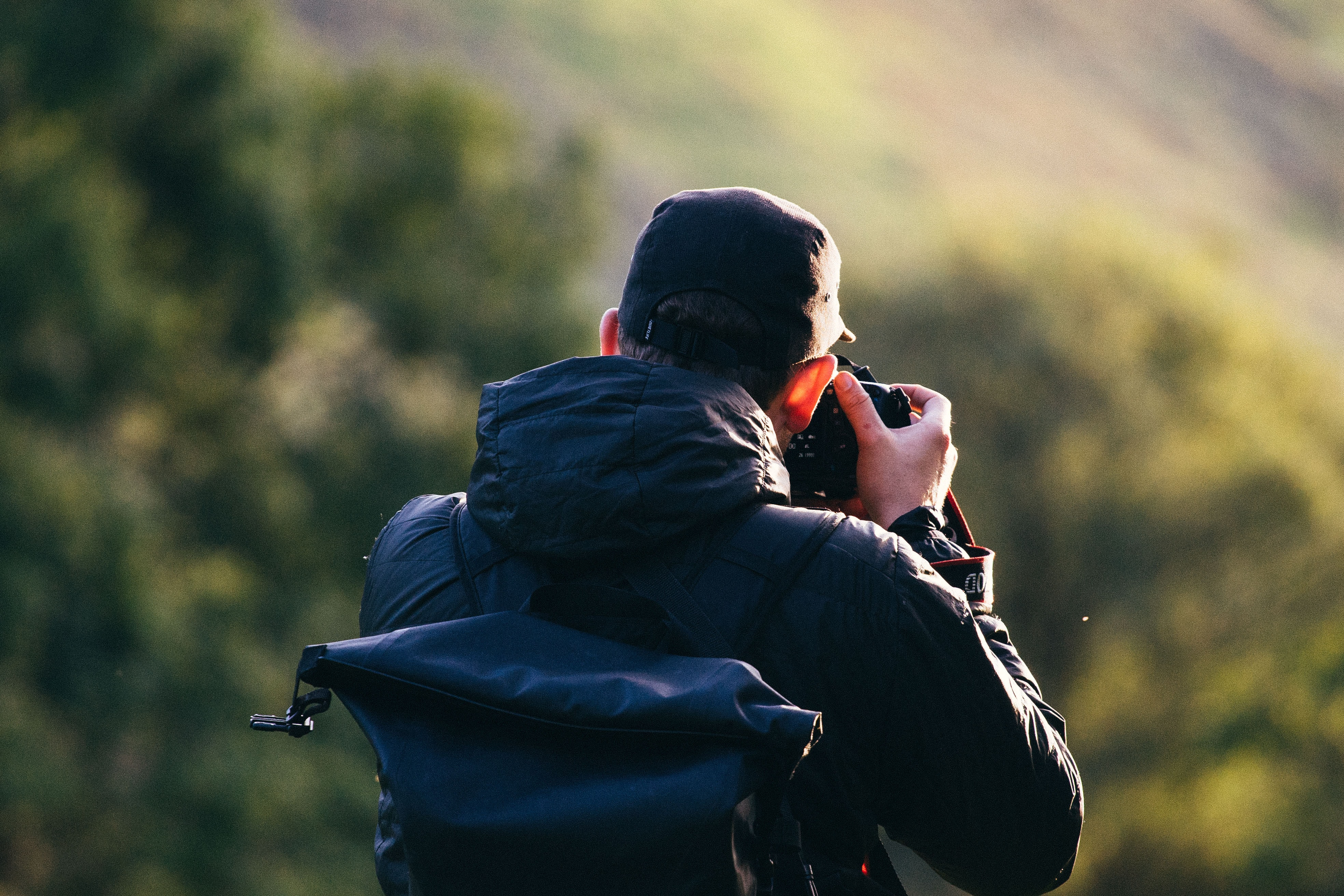A man taking a picture of grassy mountains in Snowdon, Wales