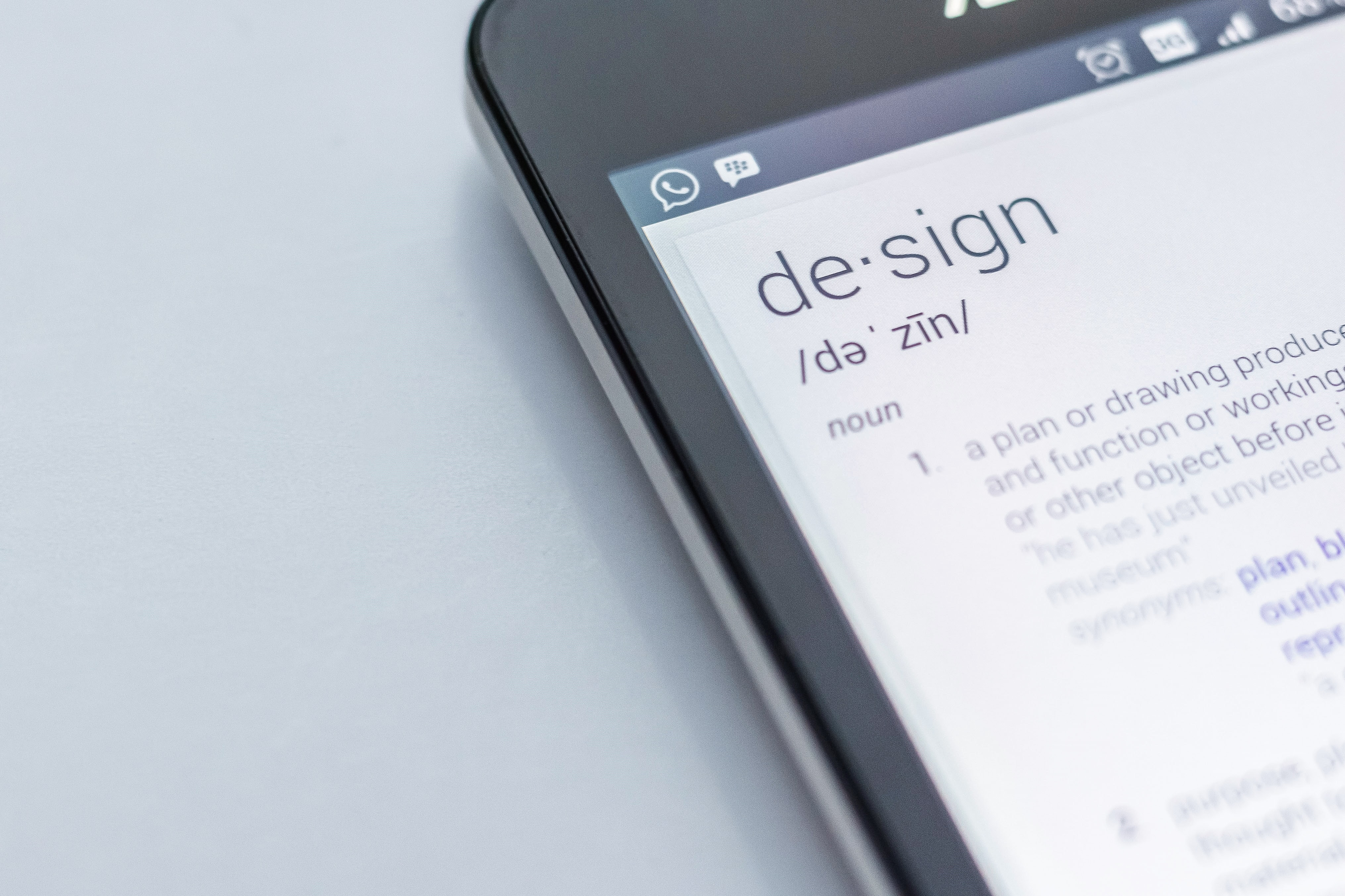 "The dictionary definition of the word ""design"" displayed on a smartphone screen"