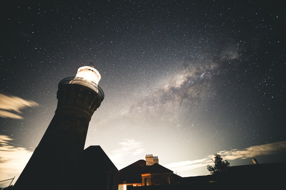 silhouette photography of house beside lighthouse