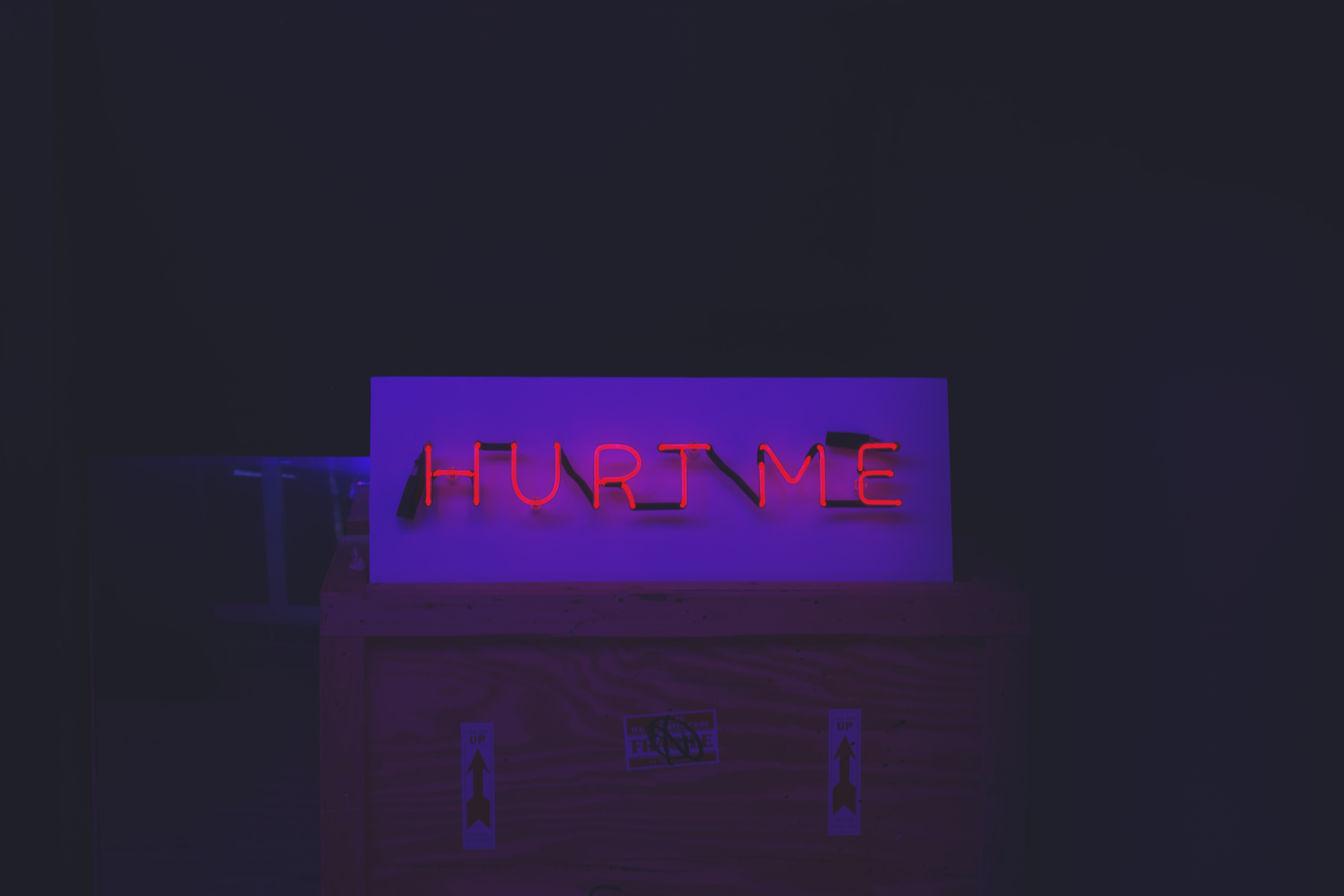 "Red neon ""Hurt Me"" sign on top of a crate with arrow stickers"