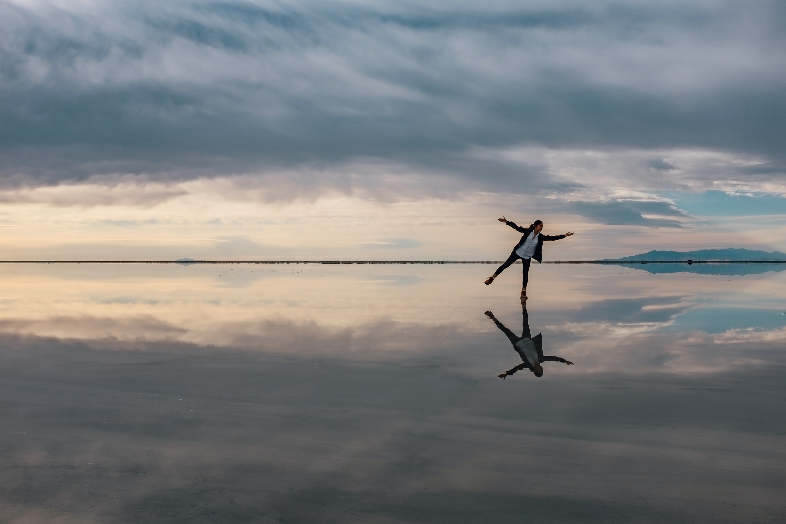 Wide angle shot of a person dancing in a seascape reflecting the sky.