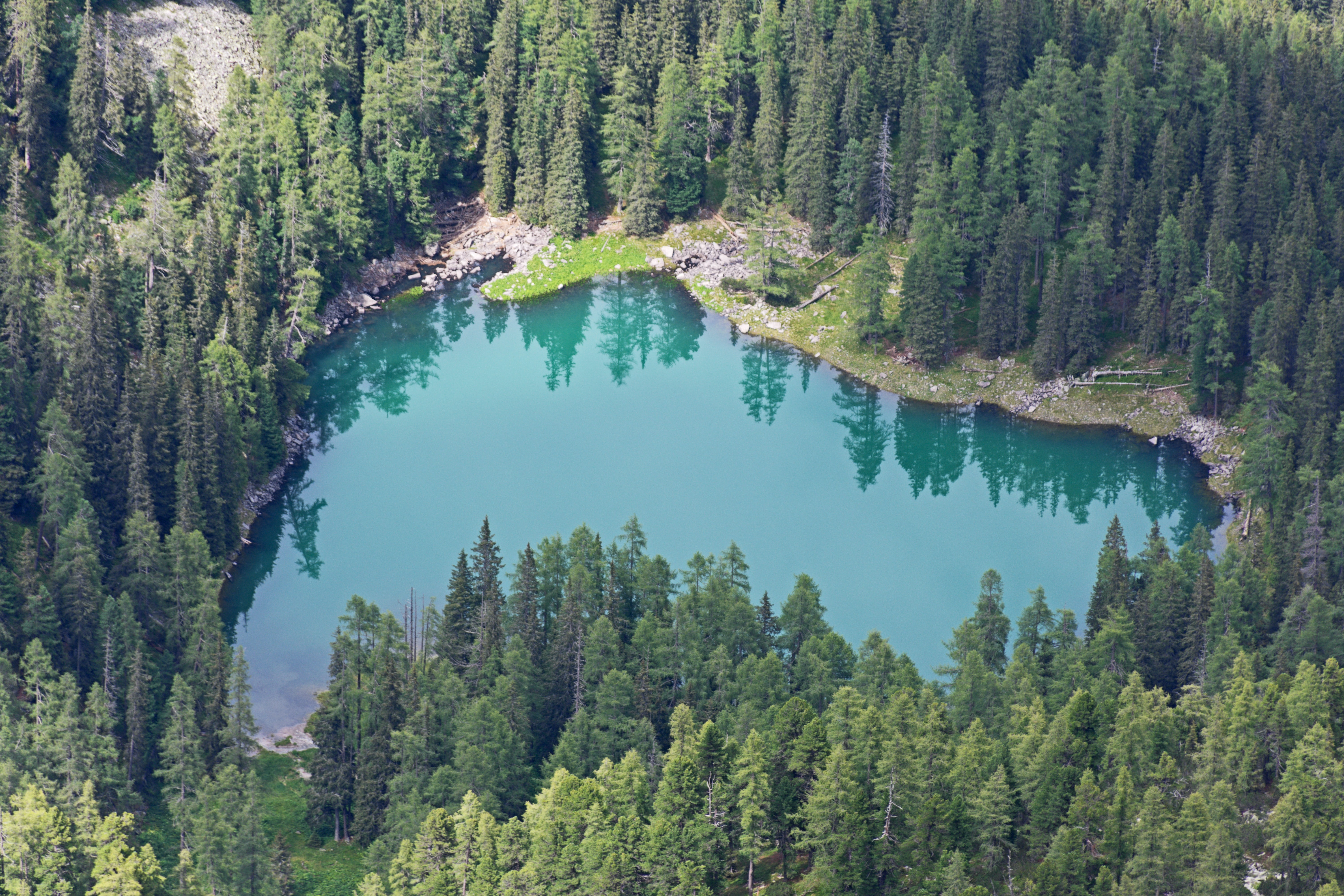 An aerial photo of a small turquoise lake encircled by an evergreen forest