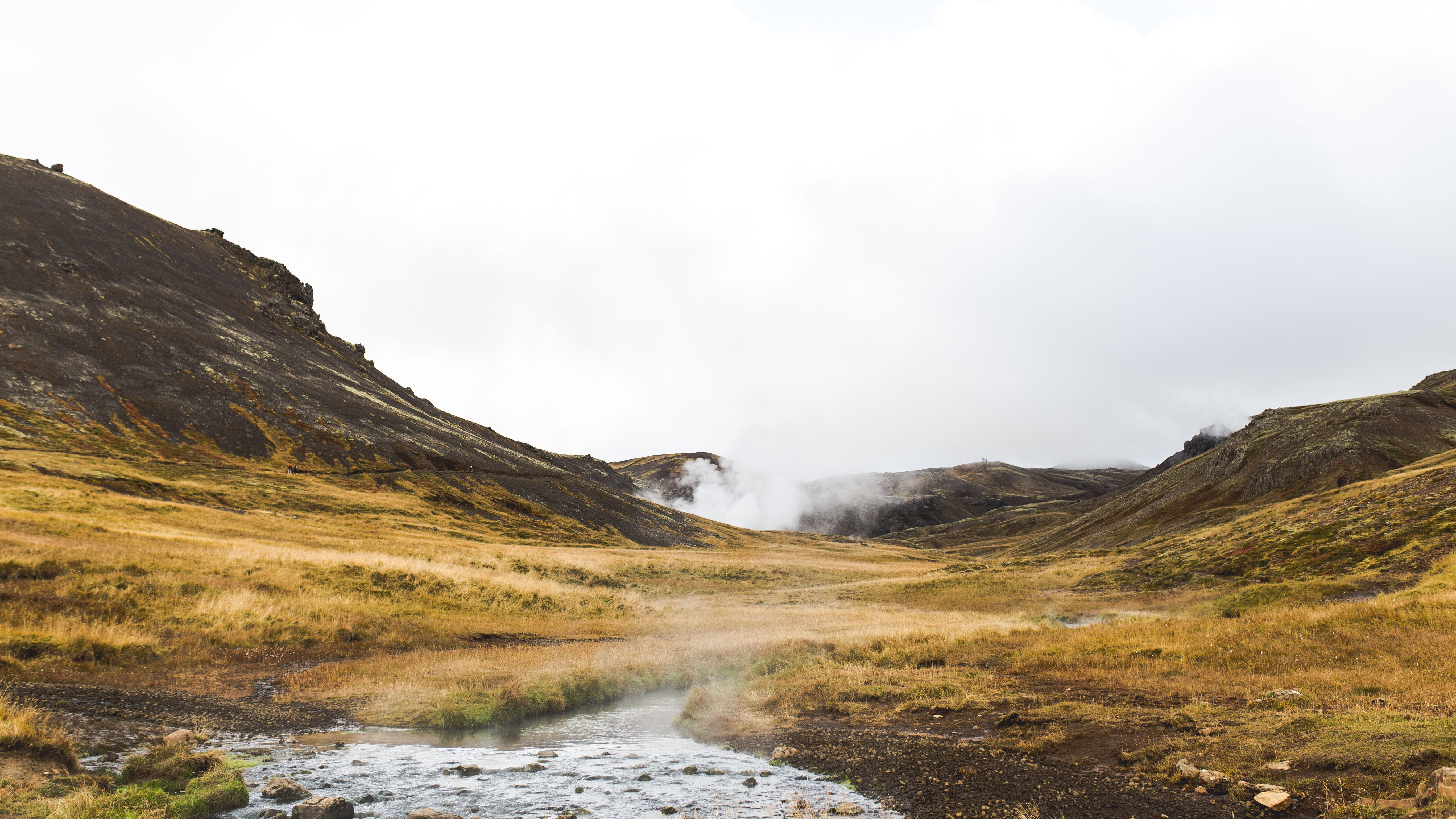 Steam rising up above a cold grassy field surrounded by rocky hills in Iceland