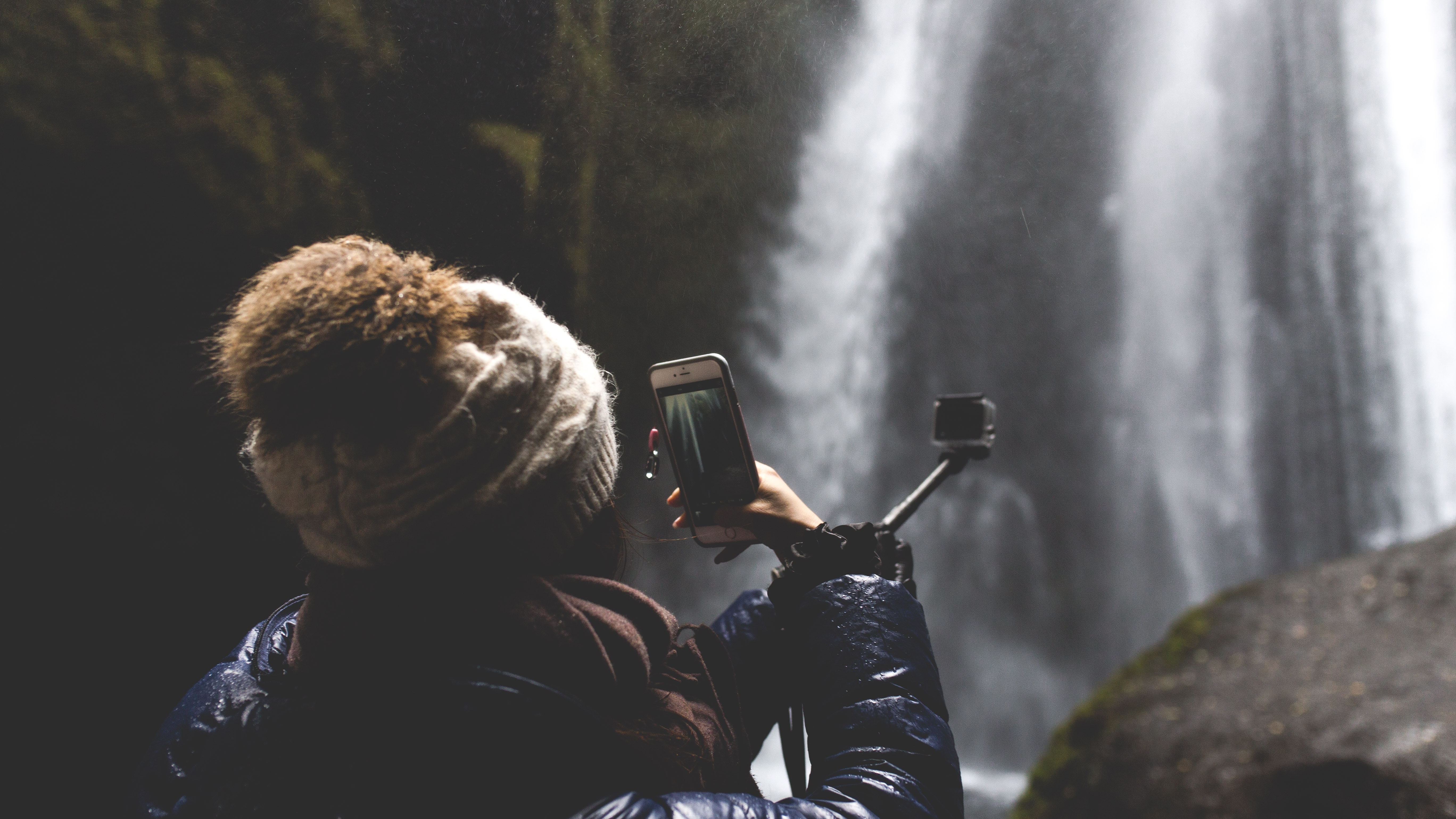 woman using smartphone and holding black selfie stick