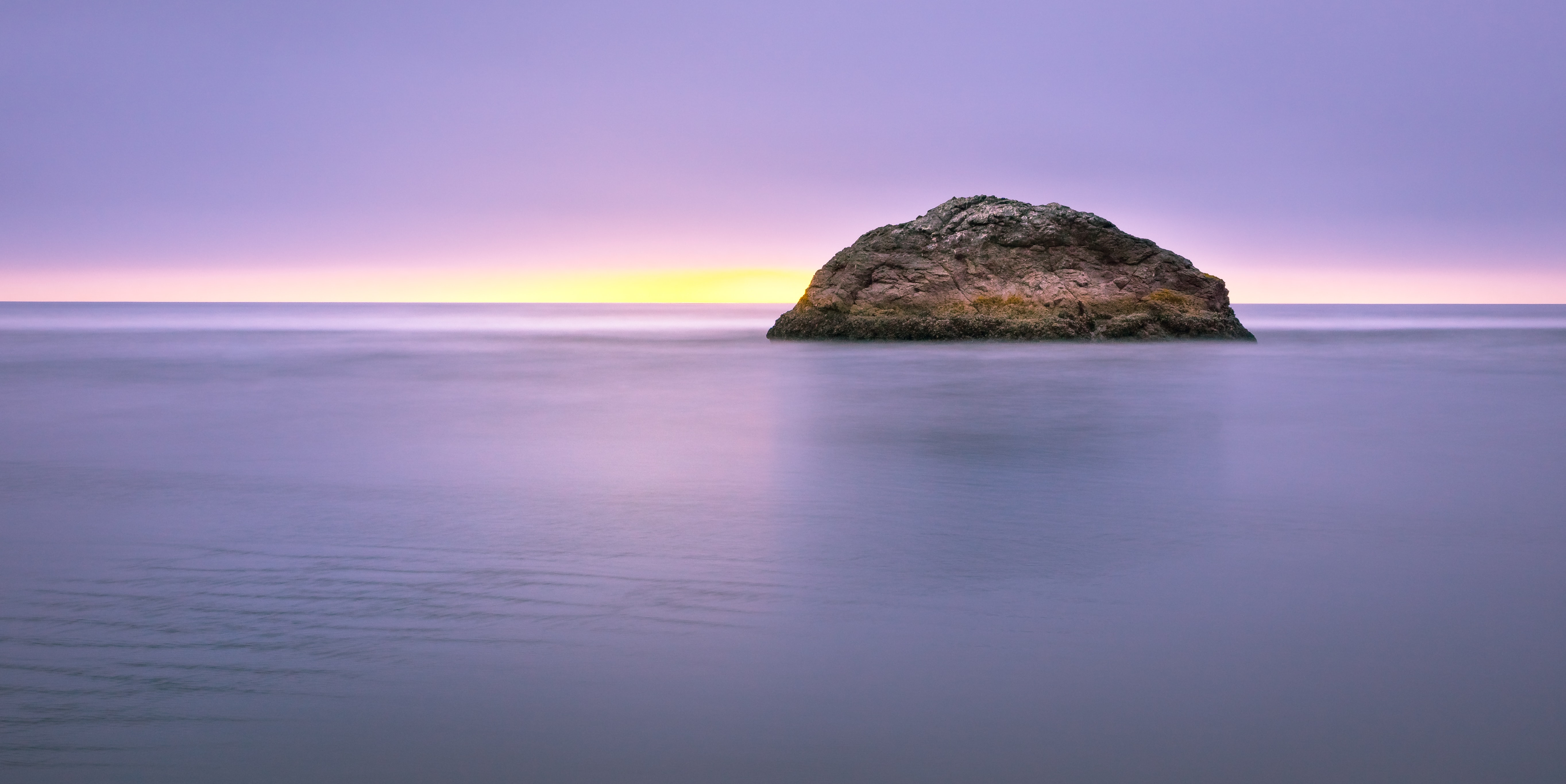 A sunset behind a single rock in the tranquil sea of Moonstone Beach Road, Trinidad, United States